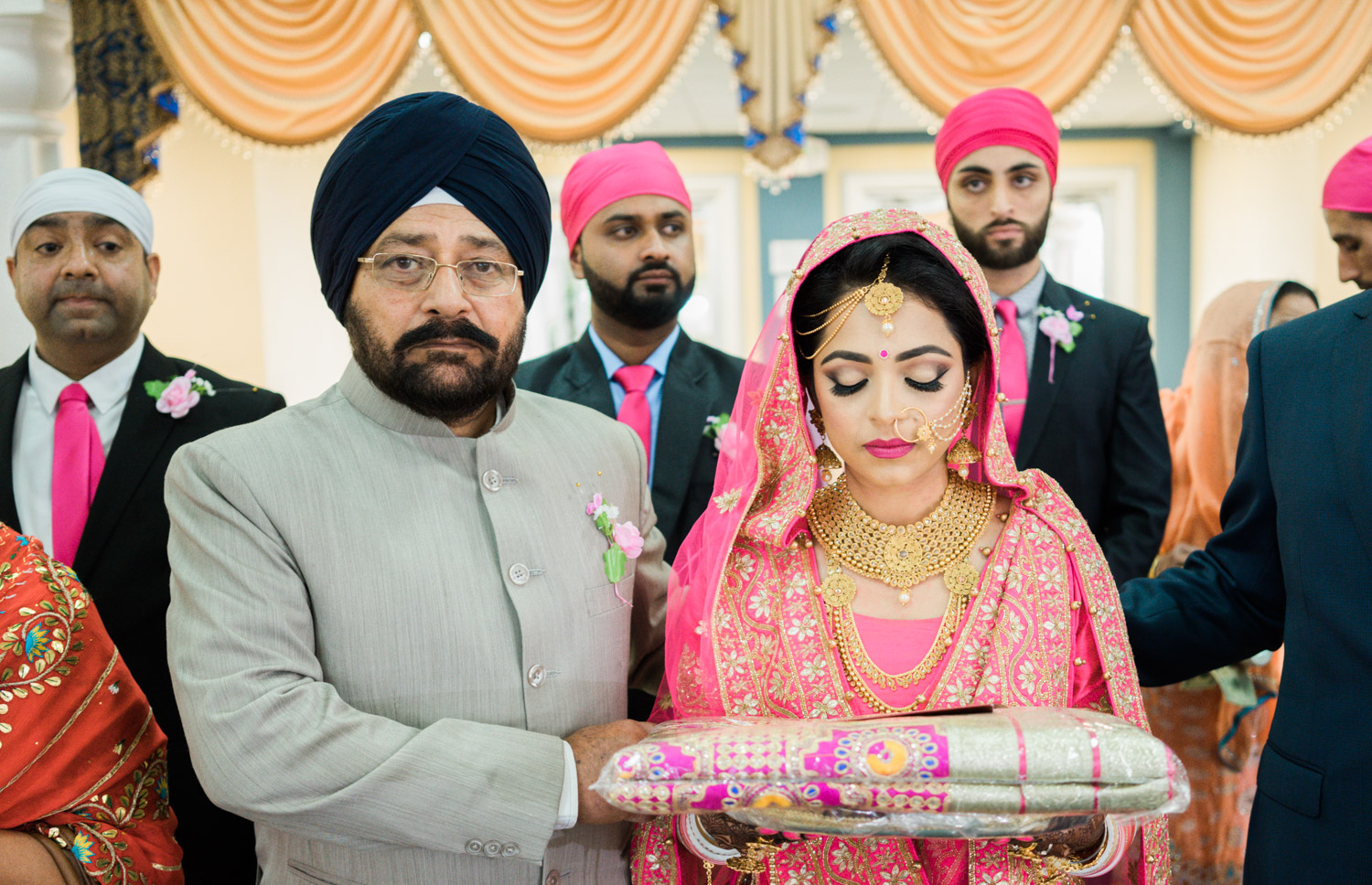 Father of the bride walks her down the aisle inside the gurudwara.