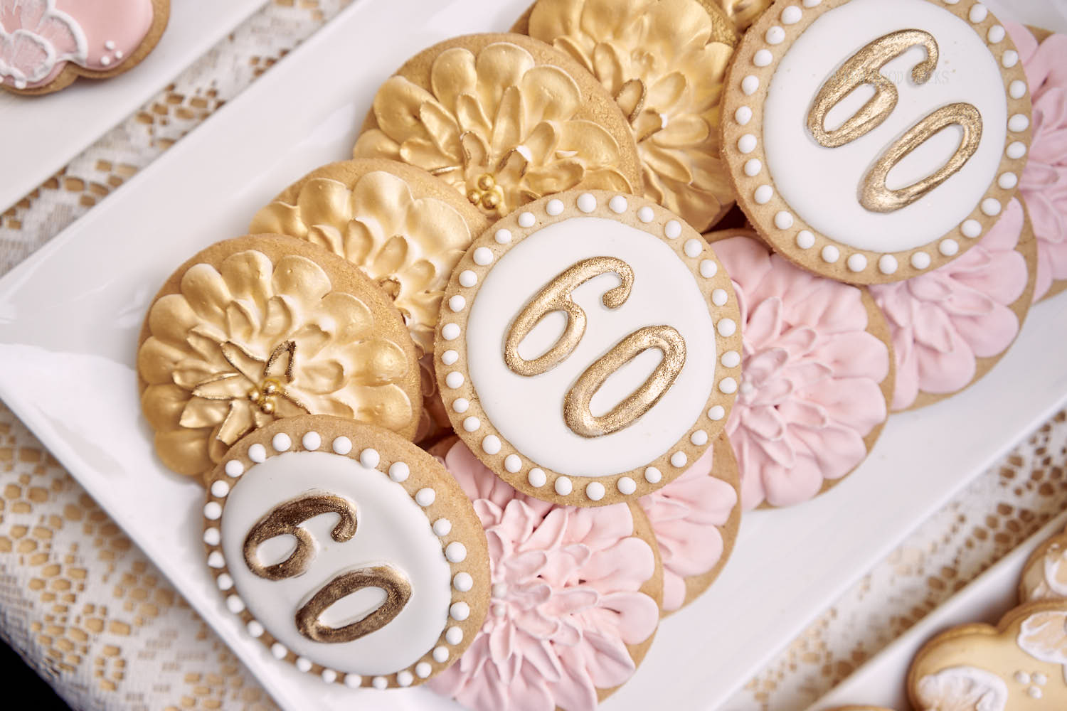 Handmade 60th Birthday cookies are hard to resist especially when they are dipped in gold & pink icing.