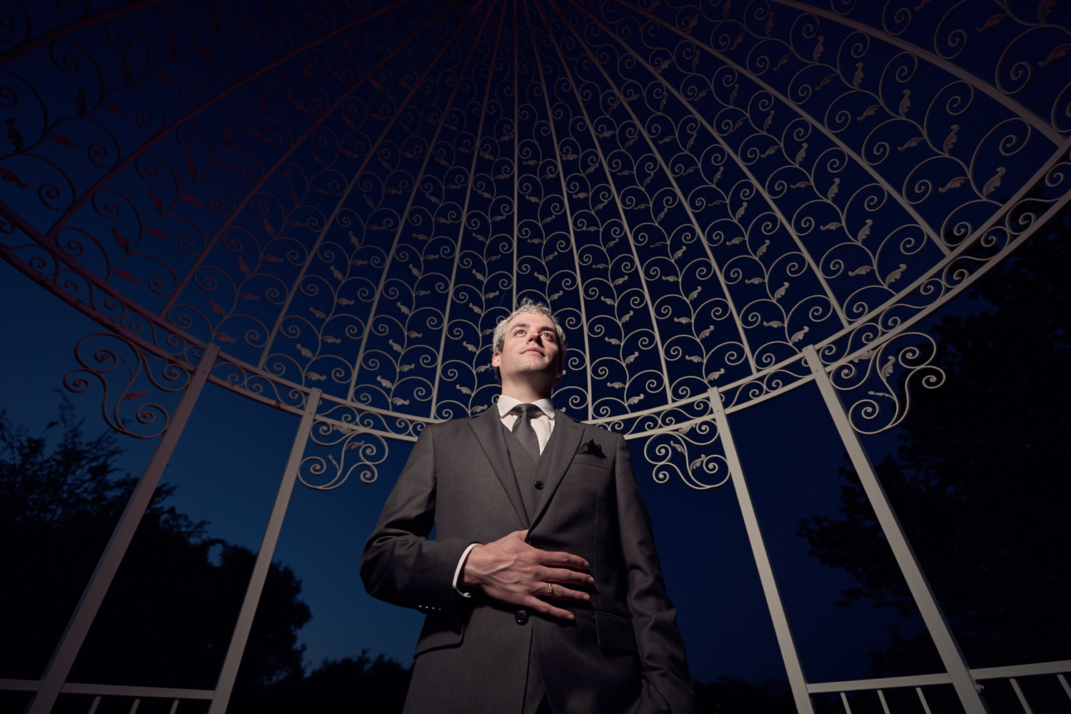 Solo portrait of the Groom under the Gazeebo.