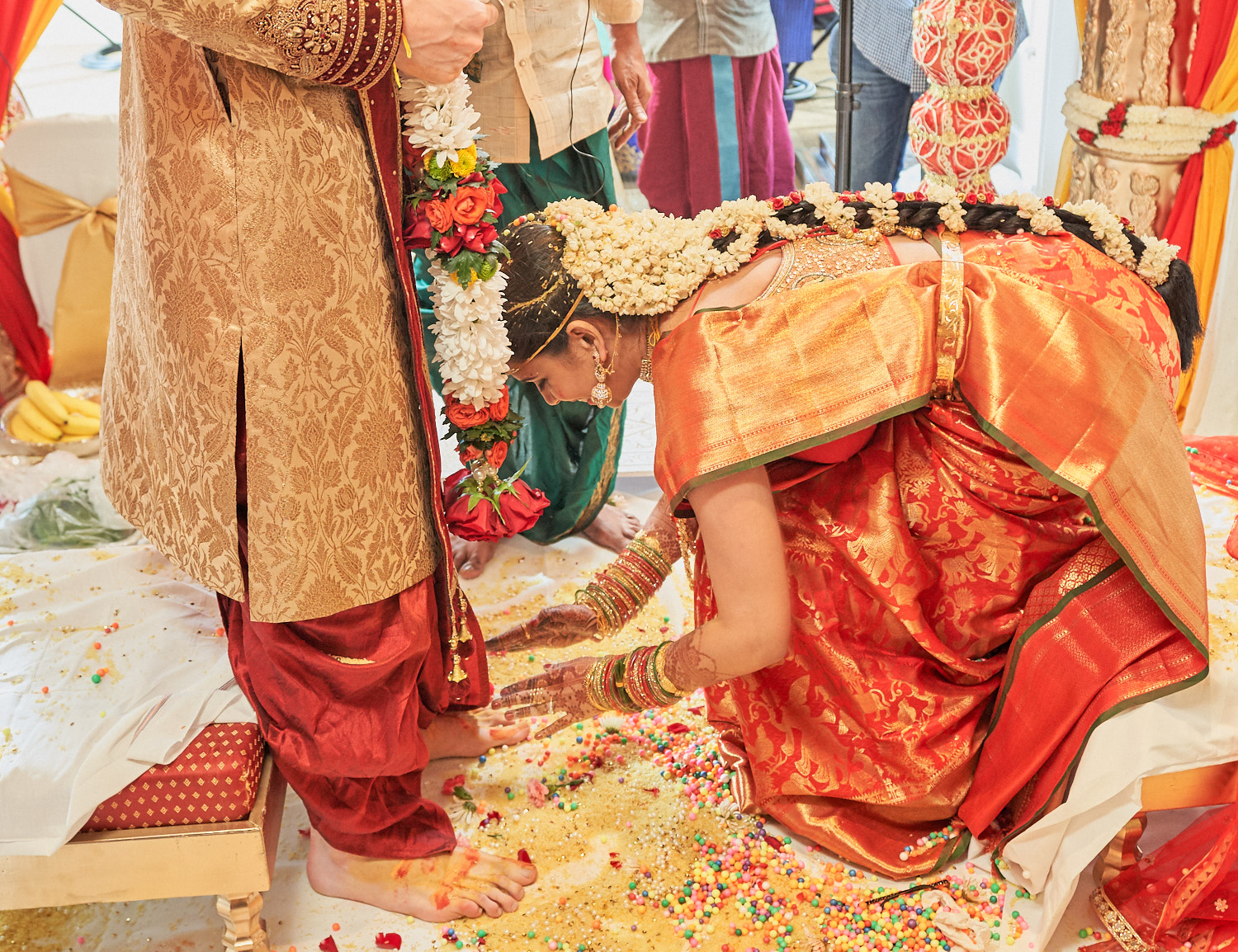 Bride touching her groom's feet - a sign of love and respect.