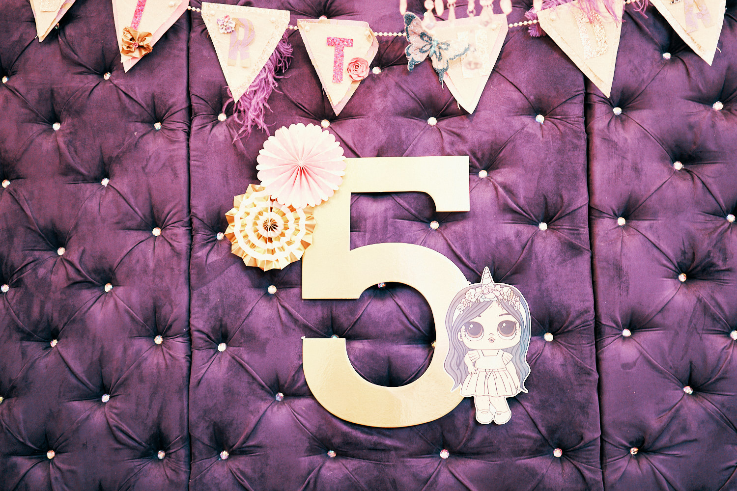 5th Birthday party signage with lol dolls decor.