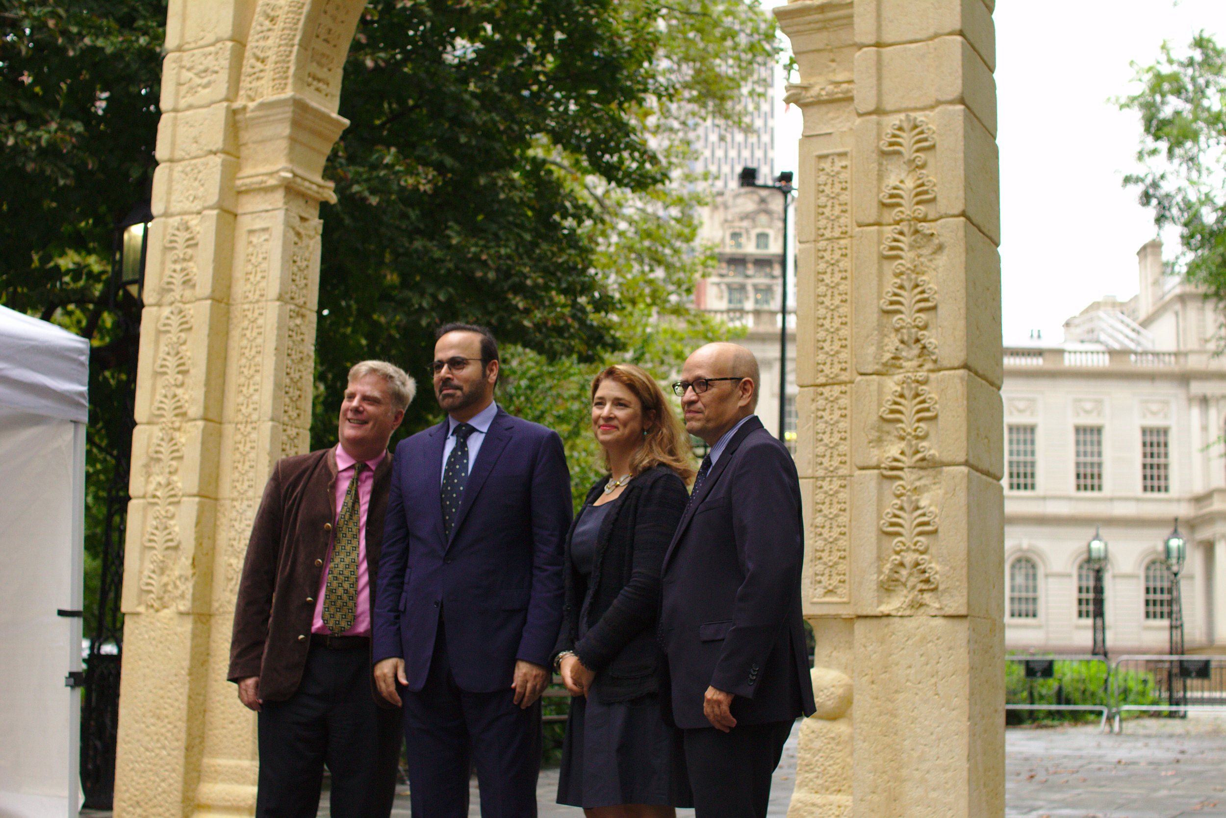 The speakers gather under the Triumphal Arch of Palmyra after its unveiling