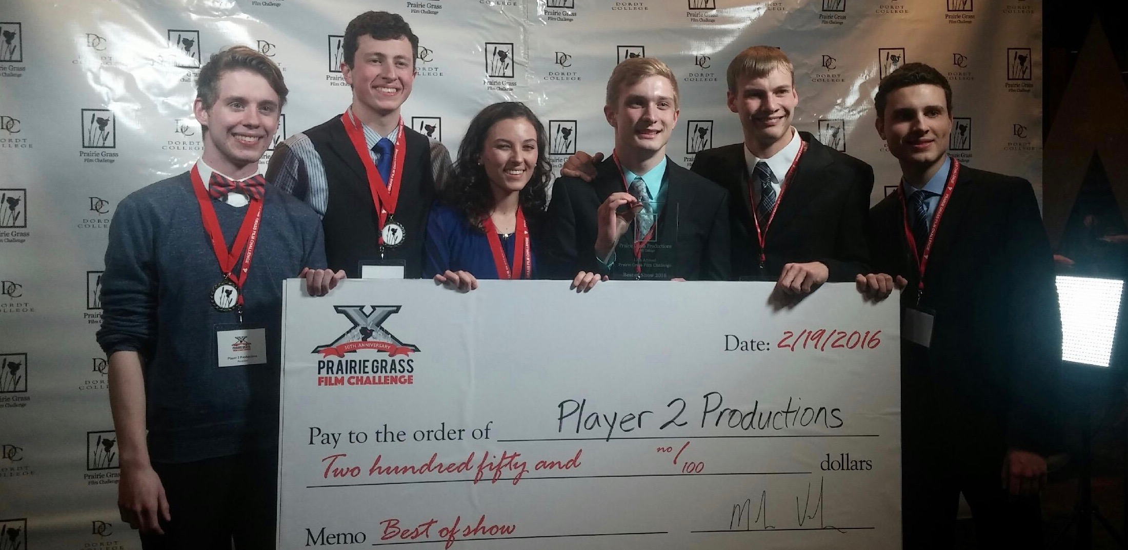 Player 2 Productions 2016 team (Nate, Cory, Annie,Ben, Josh, and Jacob) pose in front of the PGFC2016 backdrop with their newly-won check.