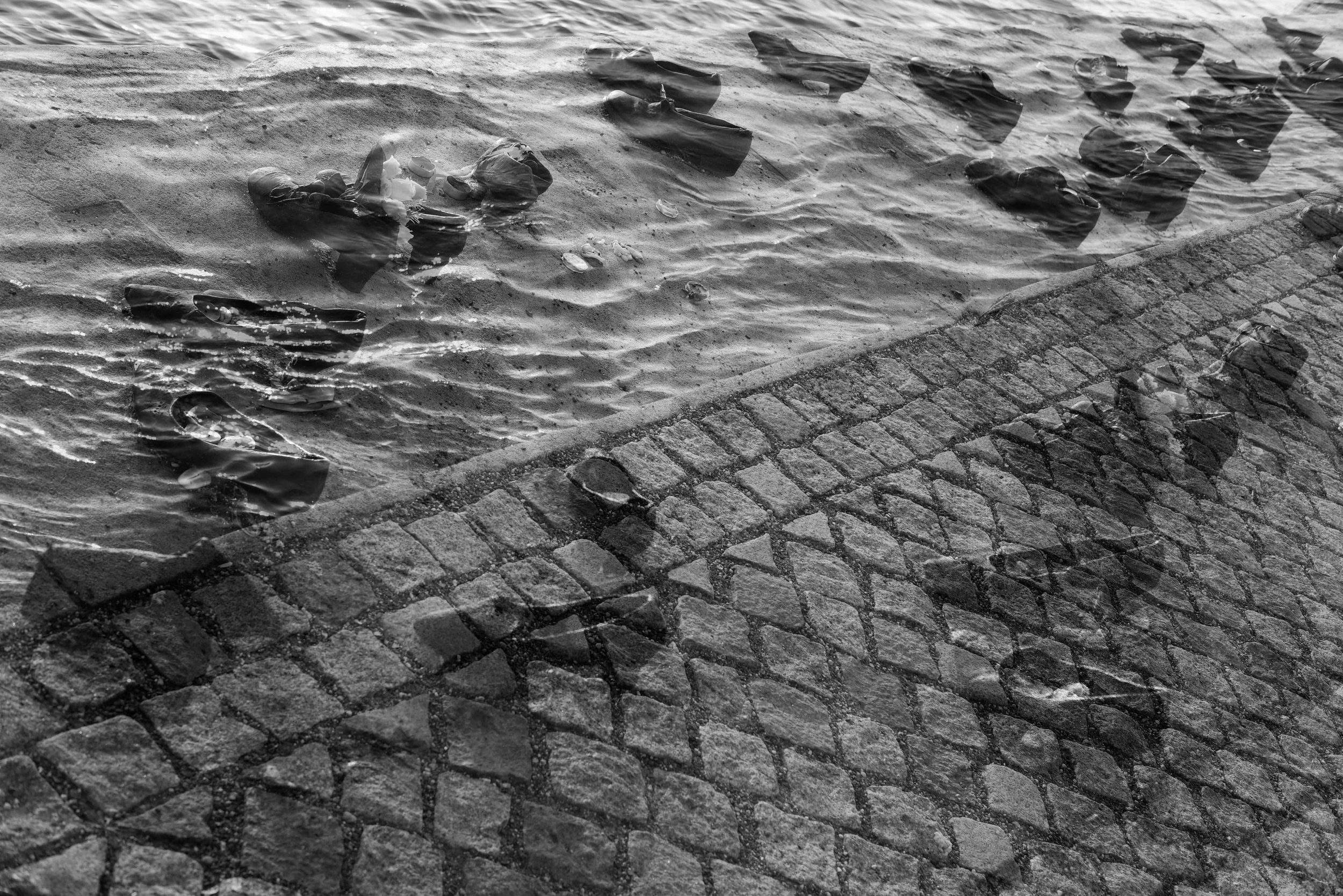 Jewish persecution during WW II. About 100 Jews were tethered together and taken to the banks of the Danube. 2 or 3 of them shot, falling into the river and pulling the rest with them to die by drowning. This is a double exposure of an art installation:cast iron shoes along the banks of the Danube.