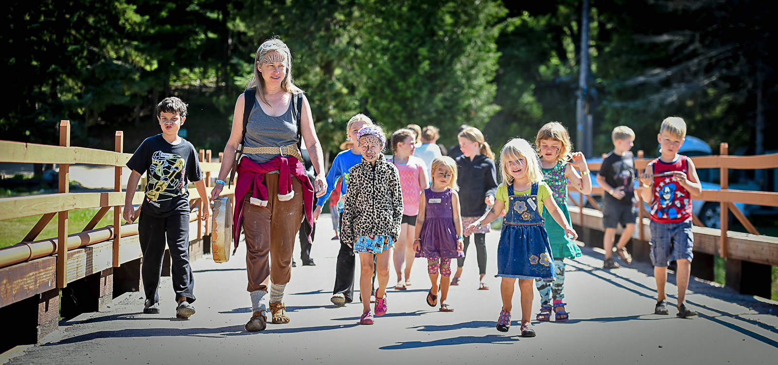Rowena Conahan leads a pack of children across a bridge spanning the Pigeon River, as part of the interactive Family Forest Village program at YogaFest 2017.