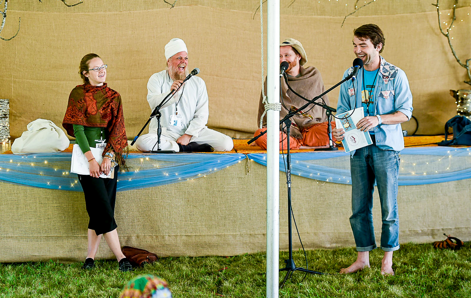 YogaFest Coordinator Brian Clark (barefoot at the microphone) shares a laugh with Assistant Coordinator Justine Markey (standing), Mohinder Singh (in white) and Trevor Chaitanya (partially obscured) during a morning Seva Meeting at YogaFest 2017.
