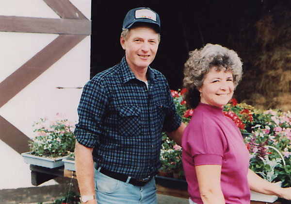 Clarence and Claire in the late 80's with the many flowers grown on the farm.