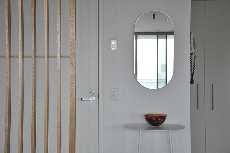 Blu Dot wall mirror to reflect the city view, and Yeh wall table making the most of limited space at the entry.