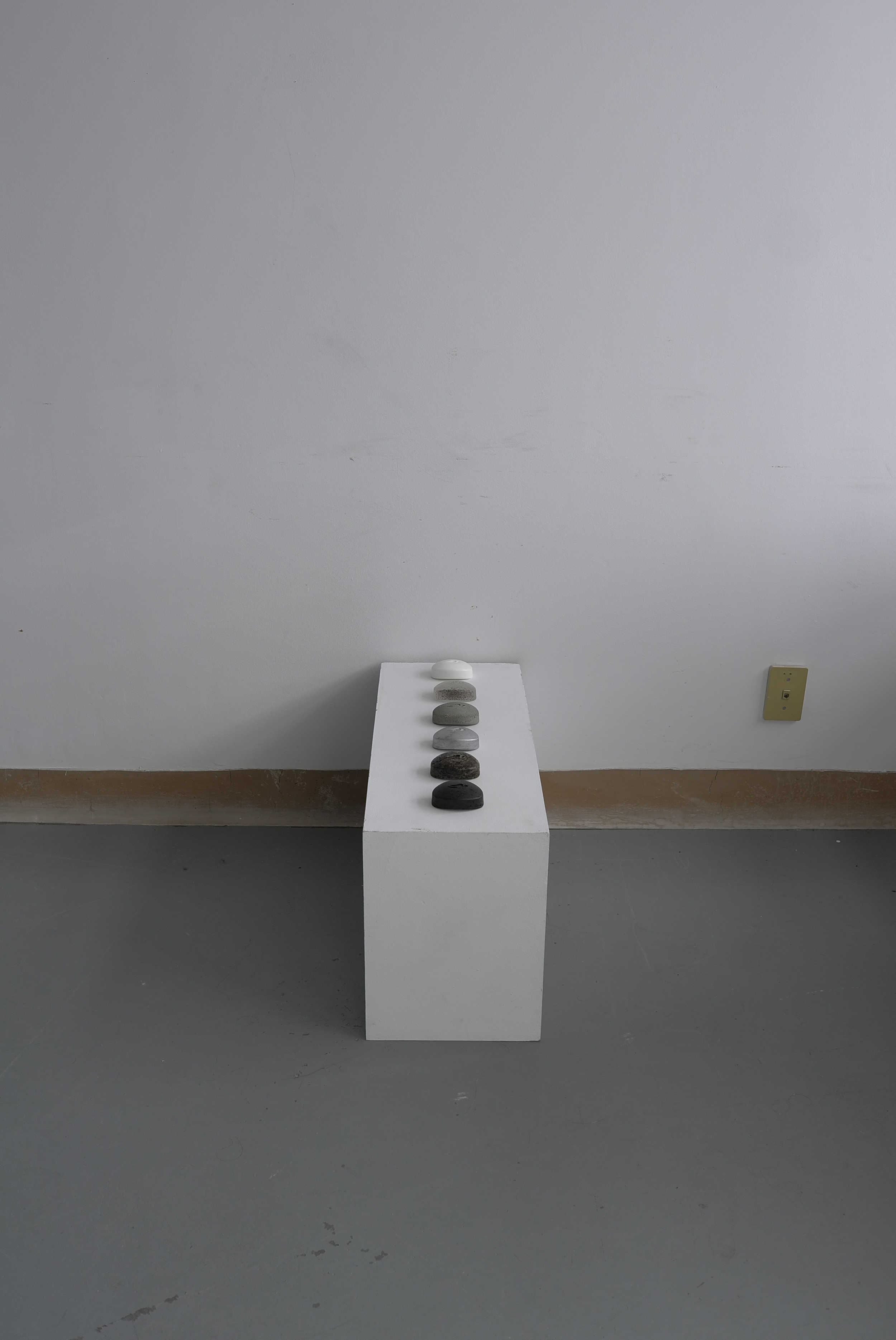View of the installation with a 'dove-soap' shaped sculptures in urban materials (aluminium, cement...) to address ideas of dirt.