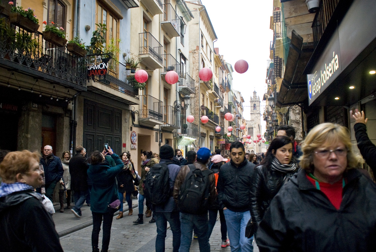 A street in the old part of the city, decked out for Fallas and filled with people celebrating.