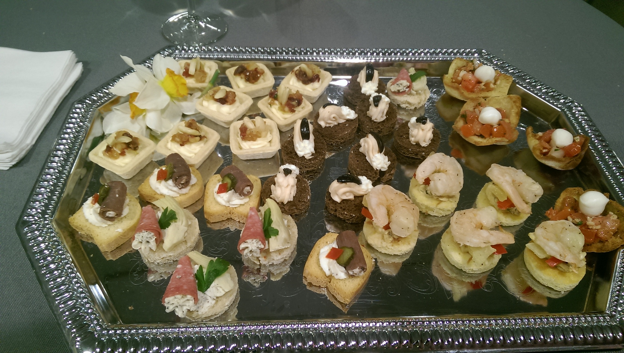 Various Passed Hors D'Oeuvres. Pictured is Roast Beef Roulades, Salami Trumpets with Artichoke,Grilled Shrimp with Pineapple on Coconut Jalapeno Cornbread, Salmon Mousse on Pumpernickel,Bruschetta in Pita Cups, and Baked Brie Cups with Fruit
