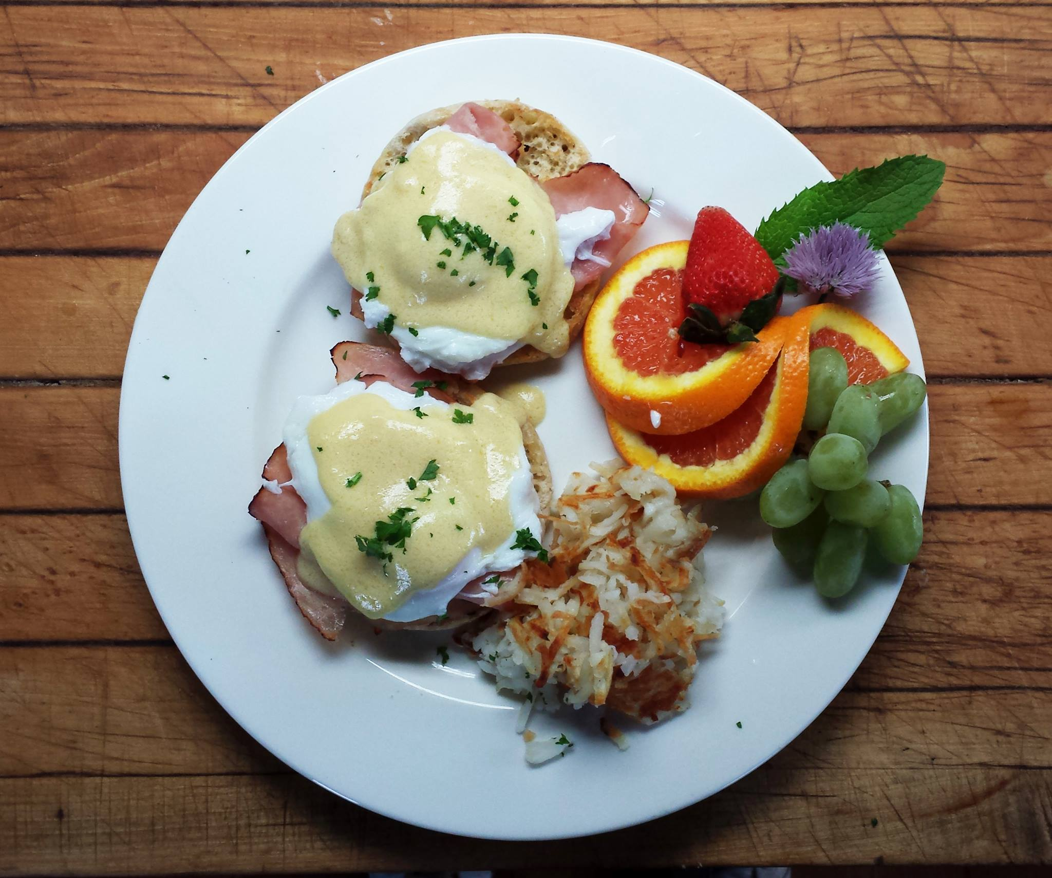 A breakfast plate of Eggs Benedict with Hash Browns and Fresh Fruit