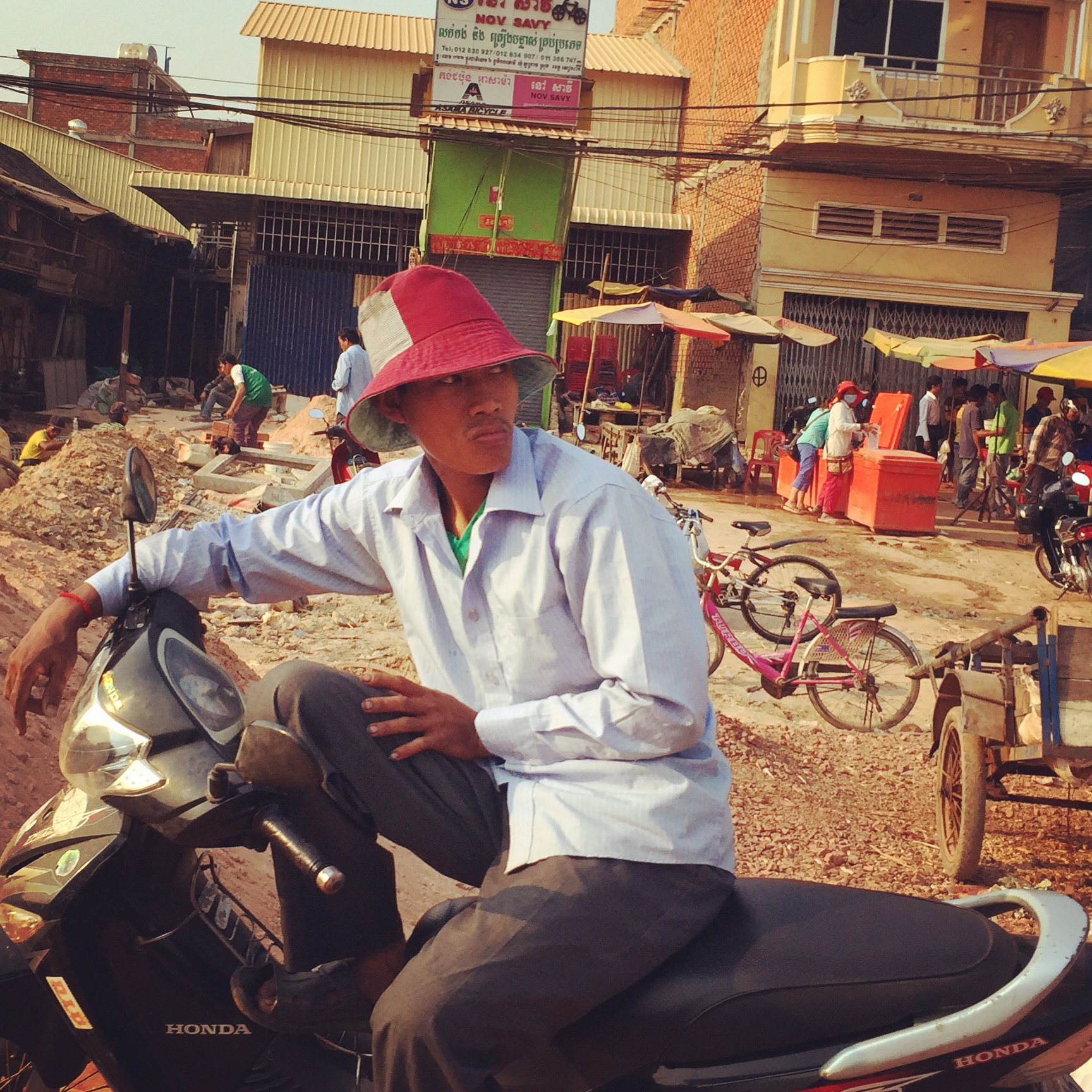 A man hanging out on his motorbike on a street in Siem Reap, Cambodia