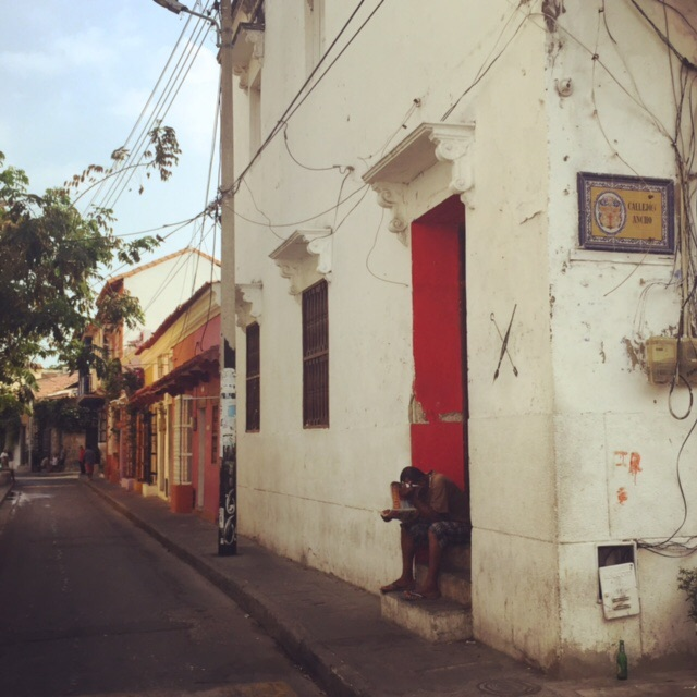 A man reads the paper in his doorstep on a quiet Cartagena morning