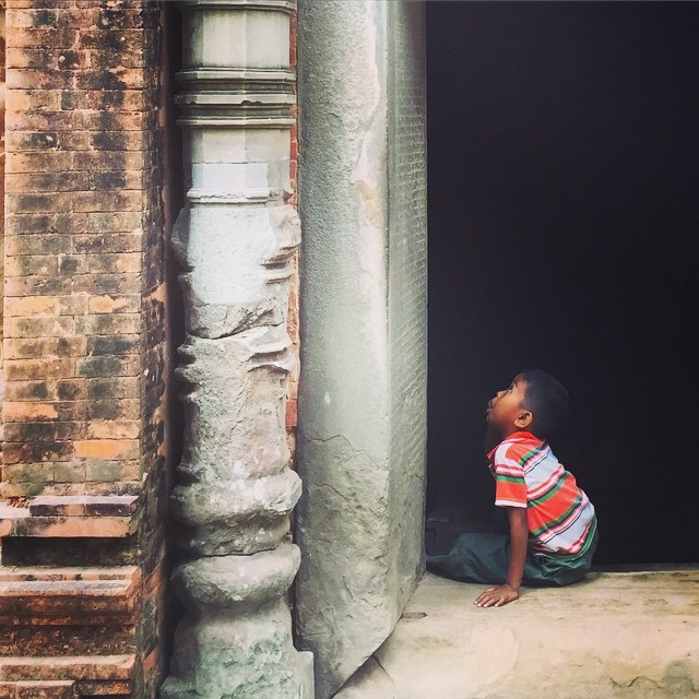 A local boy reads the ancient inscriptions carved in a doorway at Preah Ko, one of the Roluos Temples in Angor, Cambodia