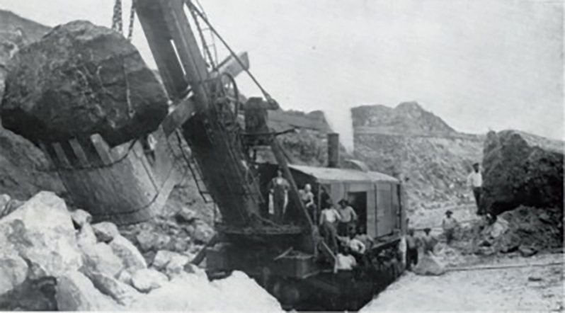 Marion Steam Shovel Model 90, 1908 image showing the shovel at work on the Panama Canal. Image taken from a 1915 Marion Shovel catalog. Image source:  MarioModel90 1908.jpg  by unknown author is licensed under  Public Domain Mark 1.0  in the United States
