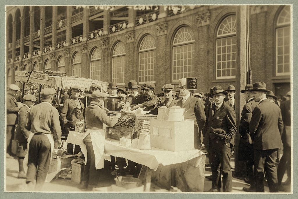 """Baseball fans--""""Hot dogs"""" for fans waiting for gates to open at Ebbets Field, Oct. 6, 1920. Image source: Library of Congress, Prints & Photographs Division,  LC-DIG-ppmsca-18463 from the  George Grantham Bain (1865–1944) collection  has  no known copyright restrictions"""
