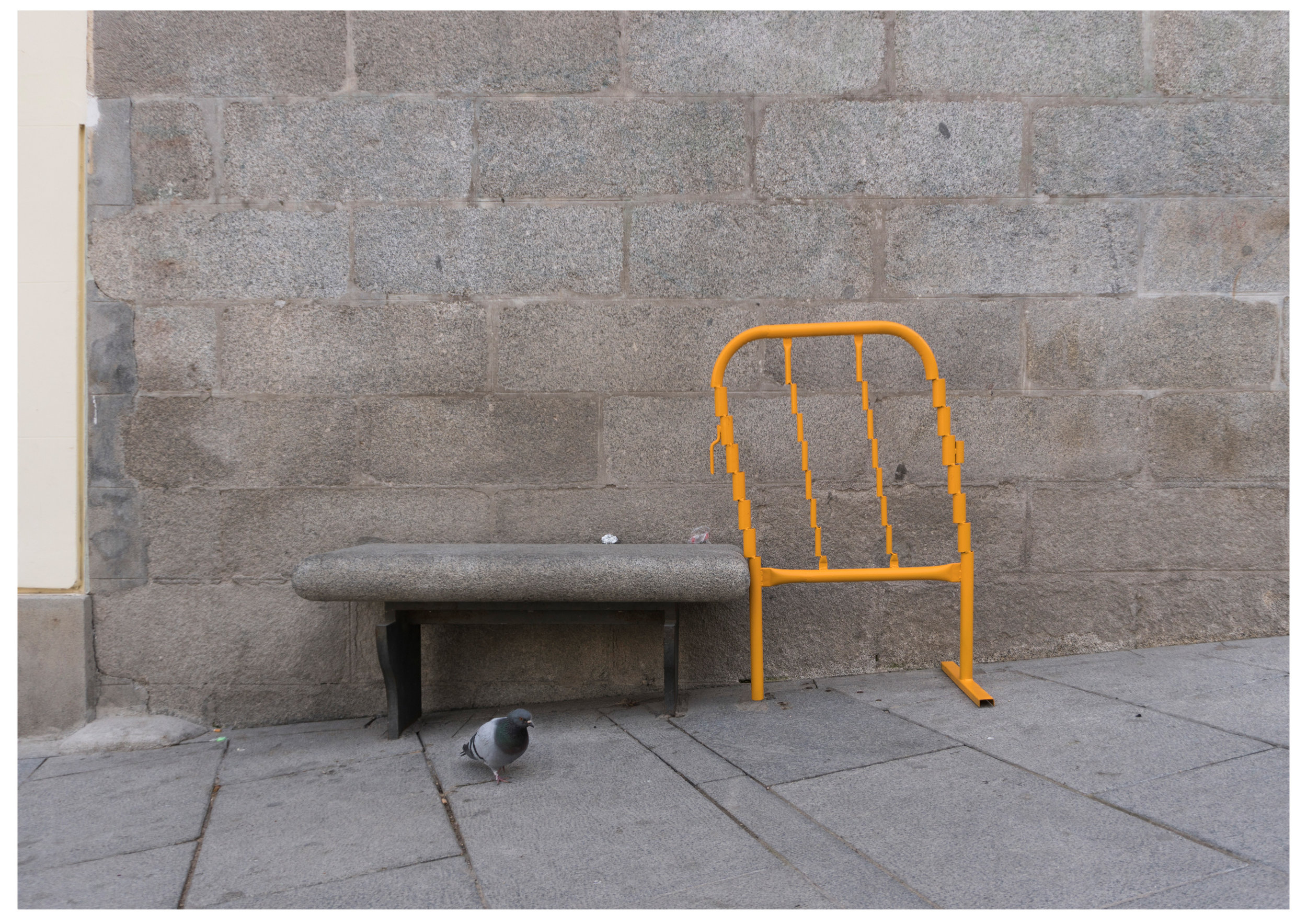 About an apparently unsecure glitchy intense yellow fence tending to rest on a presumably established cold in winter too warm in summer stone bench placed in an old steep square in Madrid
