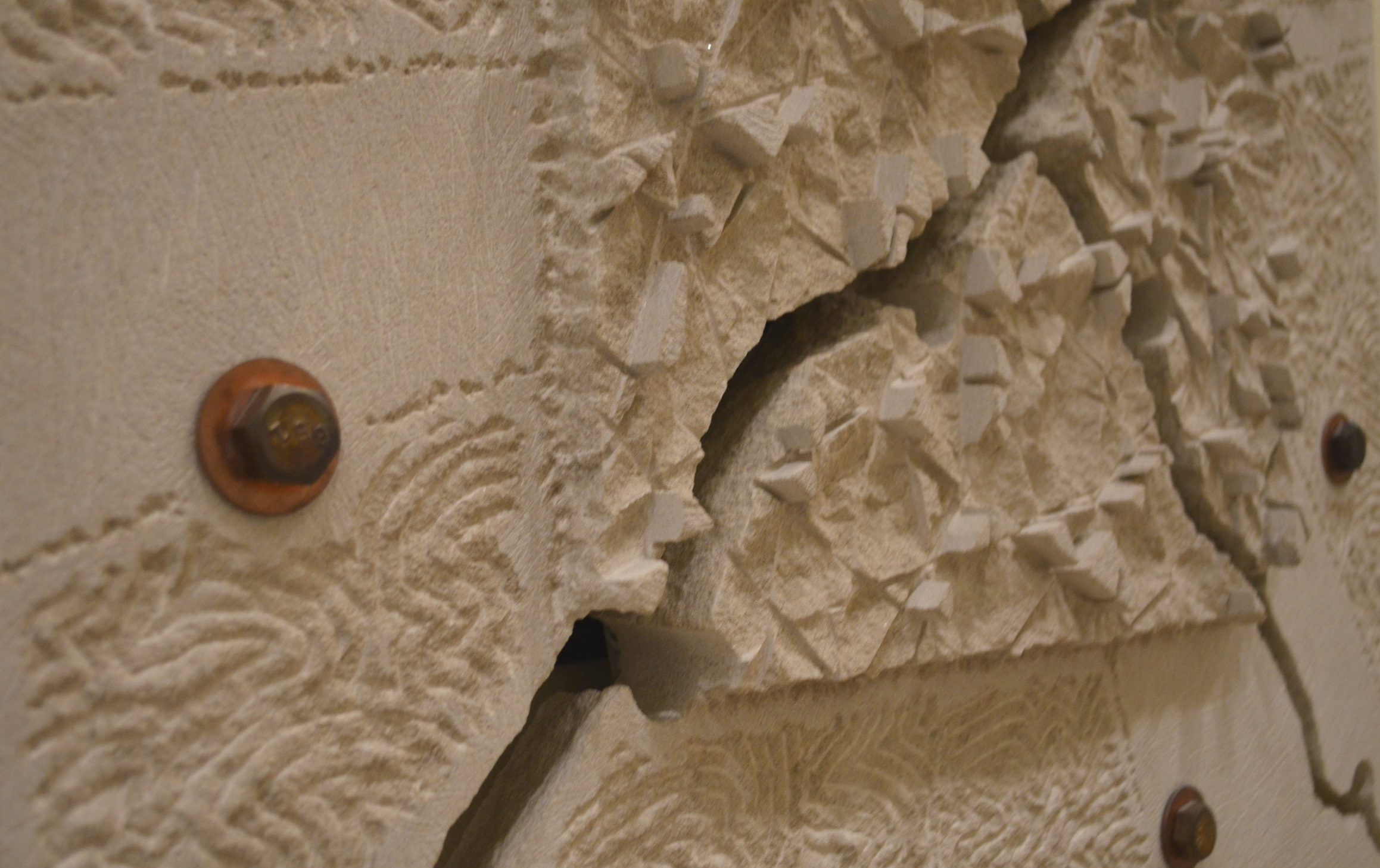 limestone wall sculpture detail image of center of mandala by dale enochs