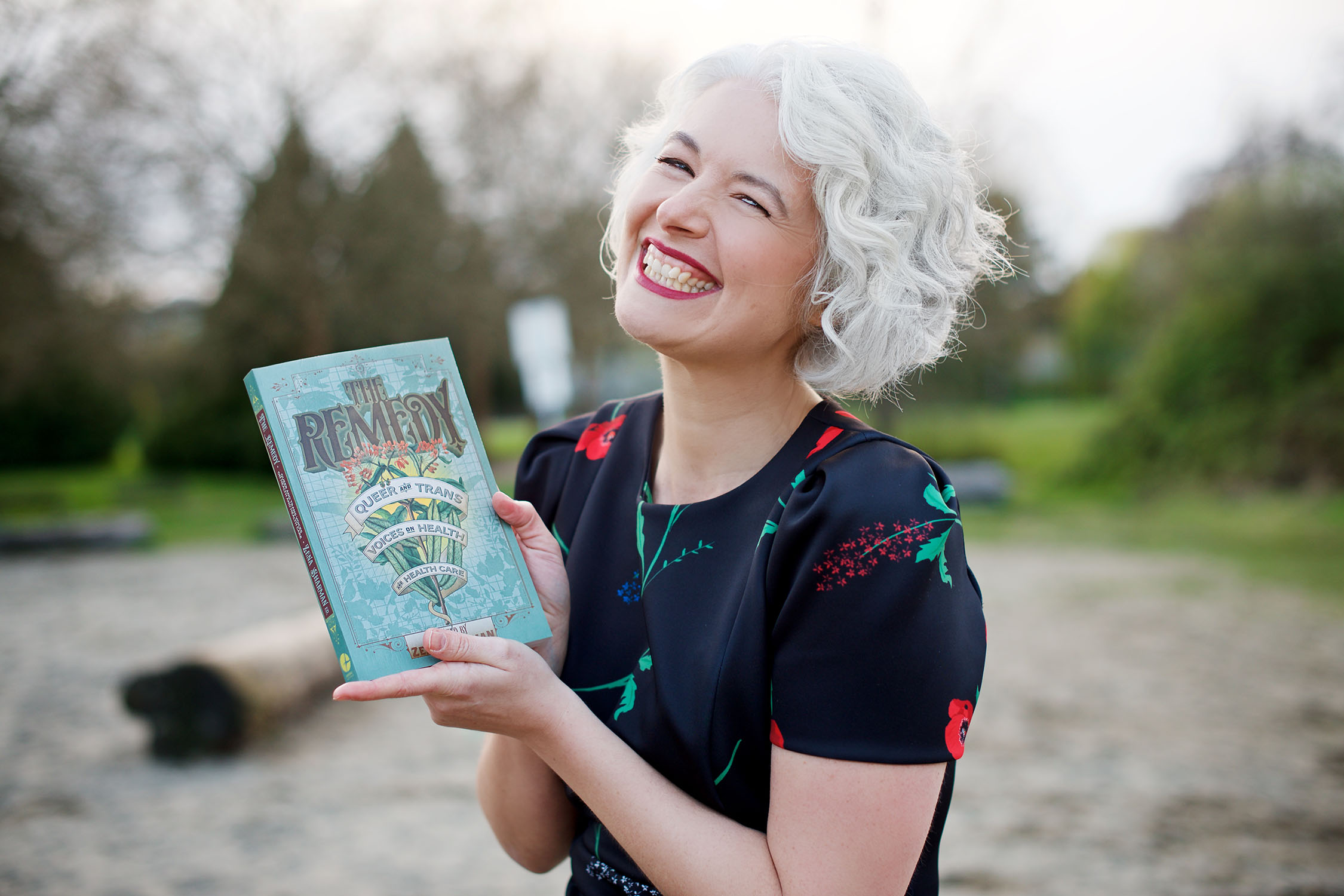 A woman smiles happily while holding a Lambda Literary award and a copy of The Remedy