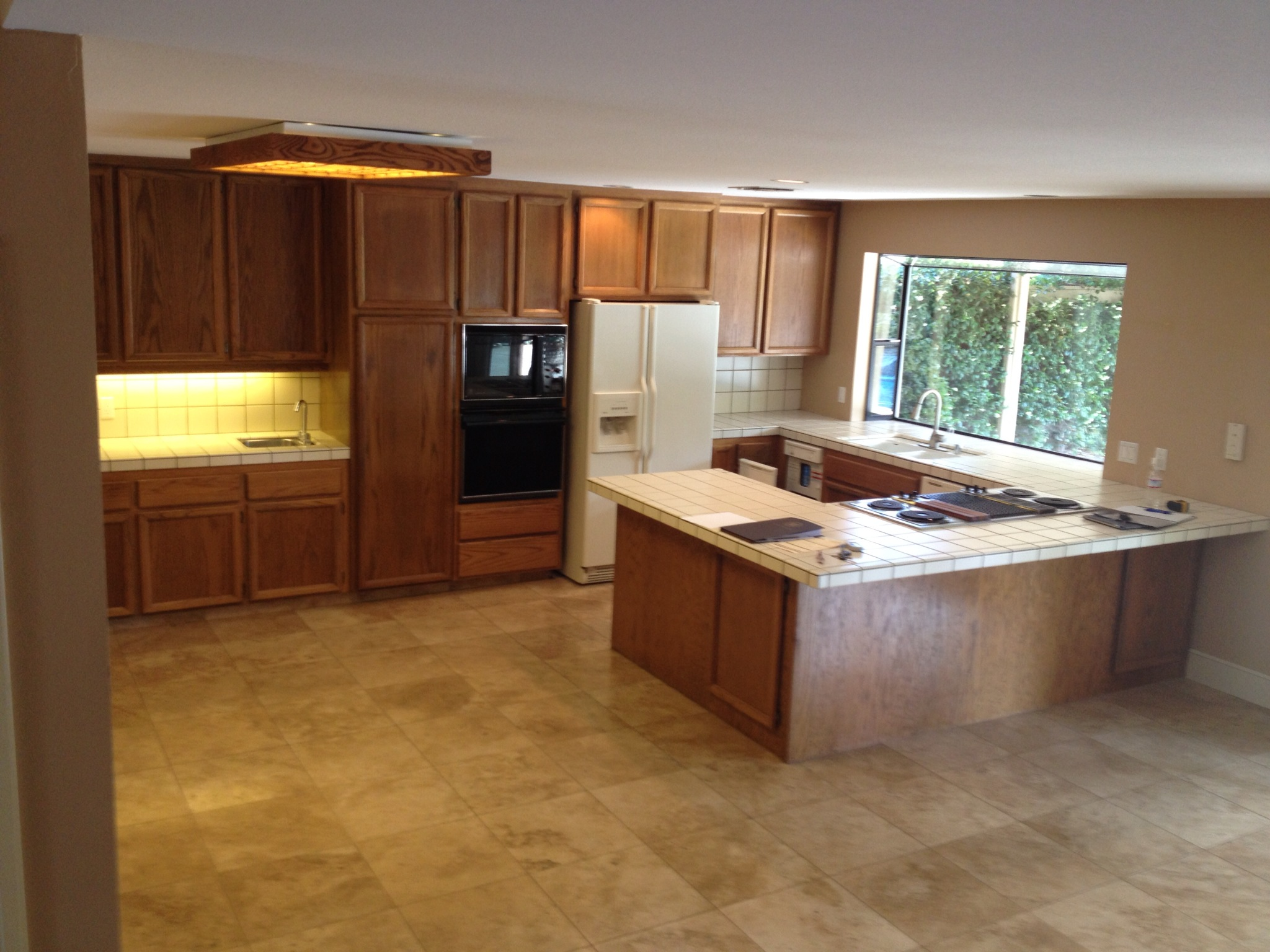 This photoshows cabinets, appliances and tile countertops that were nearly 30 years old. The layout made it difficult for more than one person to be in the kitchen or use more than one appliance at a time.