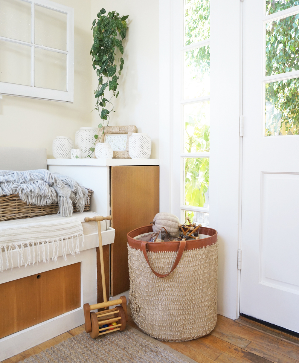 An oversized  Knotted string hamper basket contains miscellaneous toys that west enjoys daily