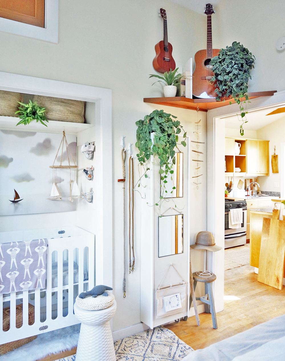 An old tv shelf above the cottage bedroom pocket door holds books, plants, tethered musical instruments, and a hanging sculpture.