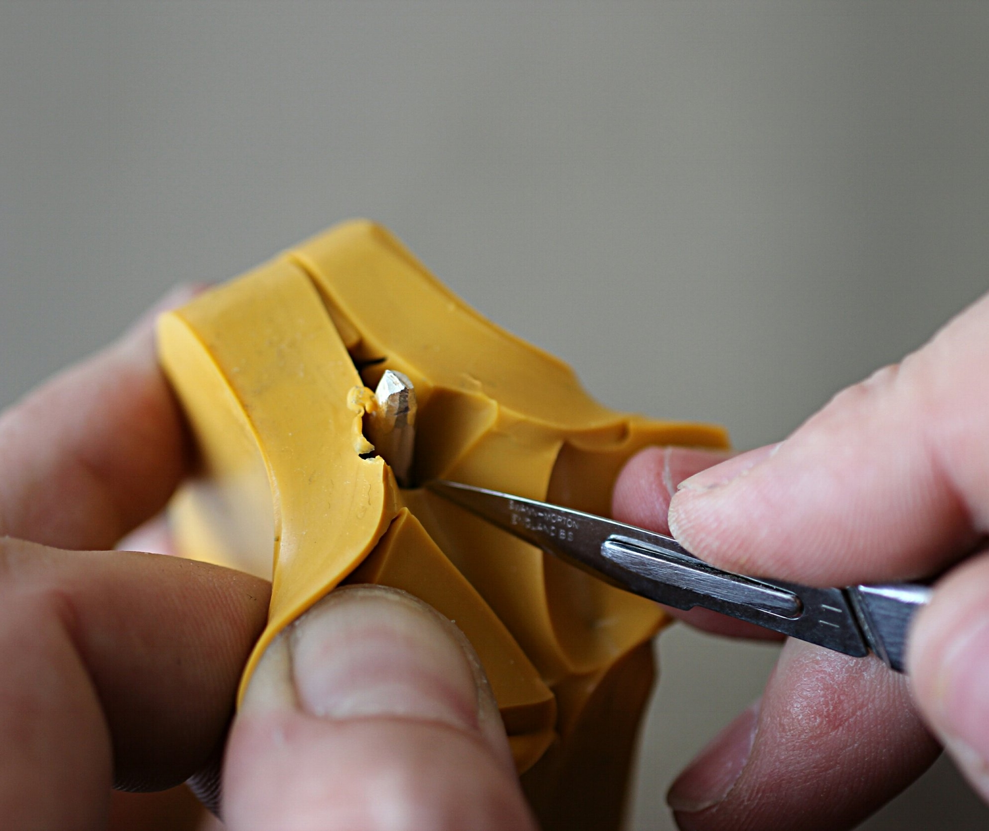 Cutting a master pattern from a rubber mould.