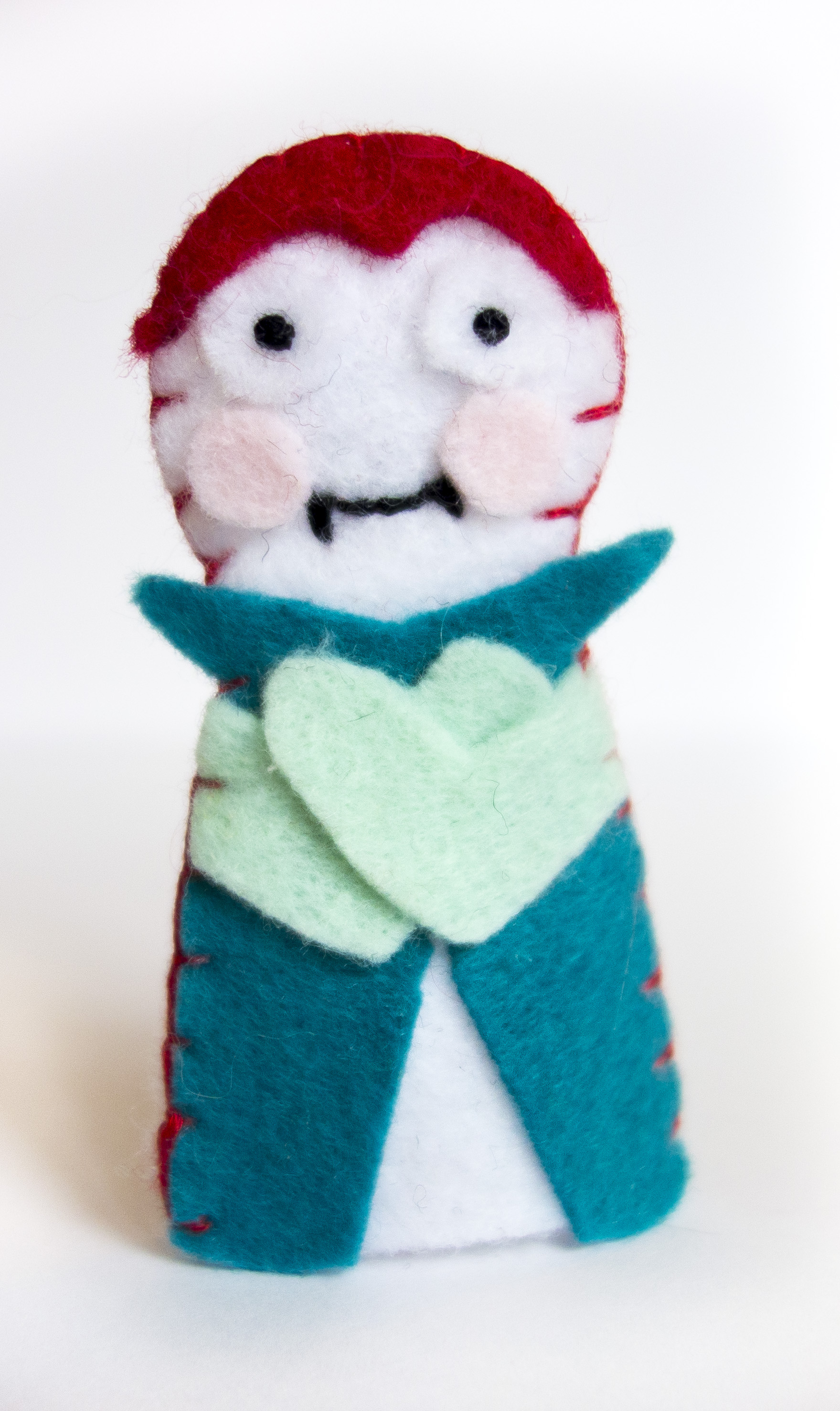 Vampire - No tricks here, just treats. Sweet pink-cheeked smile with a bite, French knot eyes, blanket stitched all along the sides.