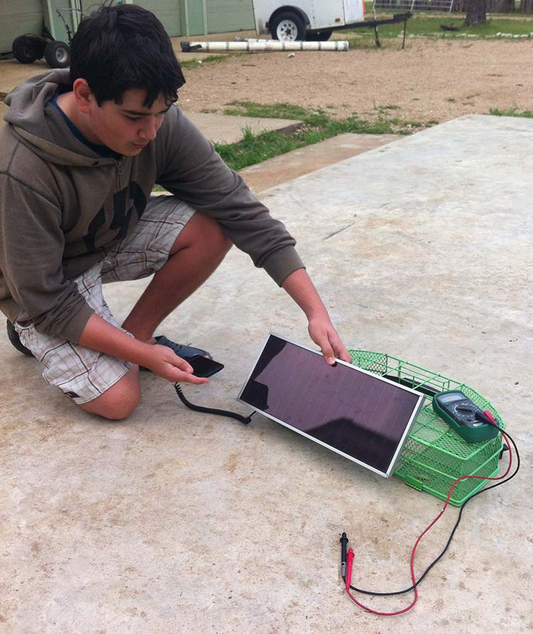 Cainan working on a solar-powered phone charger from a hacked phone charger that plugs into a cigarette lighter and a solar panel from a garage sale.