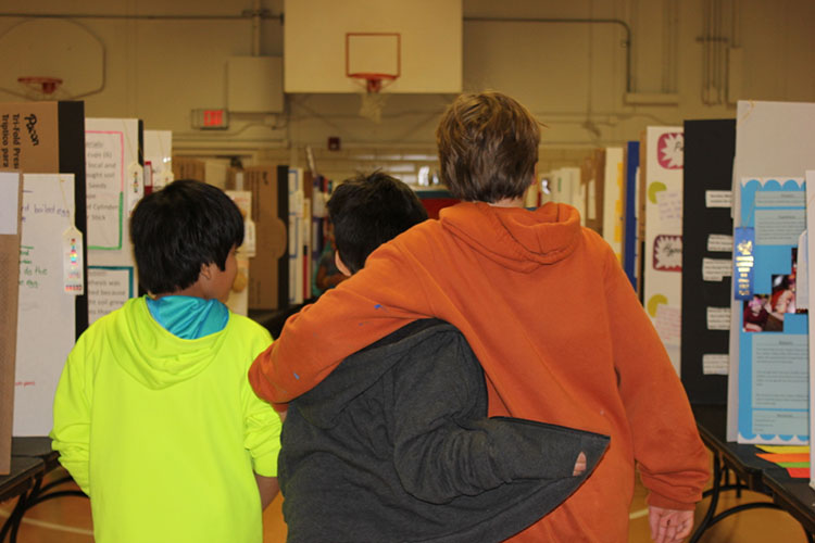 A scene from Science Fair Week at Cunningham Elementary: compassion in action. (Photo by Dawn Johnson.)
