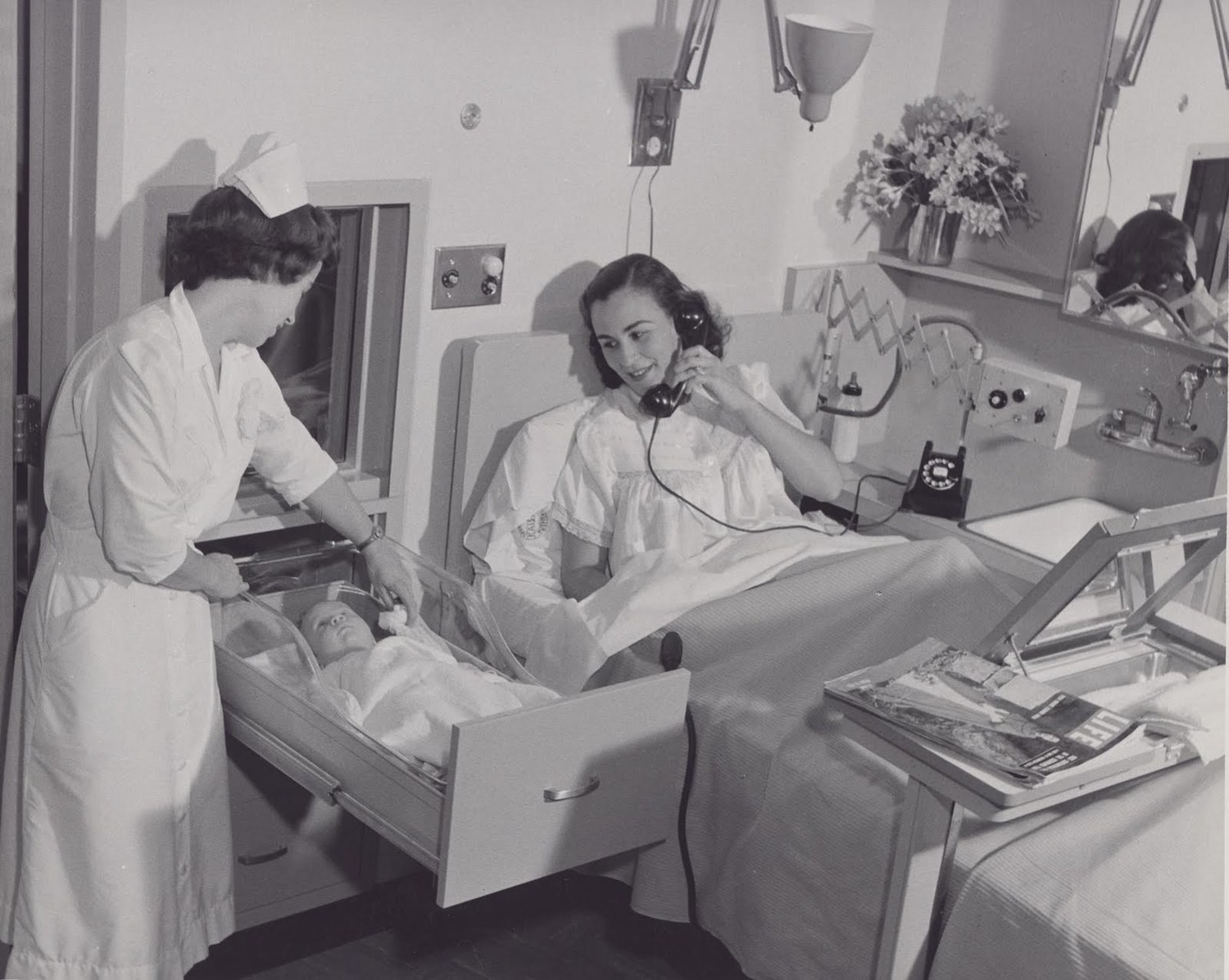 Here we see how in the olden days babies used to love hanging out inside hospital drawers and some lady holding an arcane, unidentifiable device. Photo Credit: Kaiser Permanente