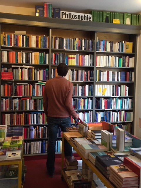 """Christopher perusing the """"Philosophie"""" section of a used book store in Berlin."""