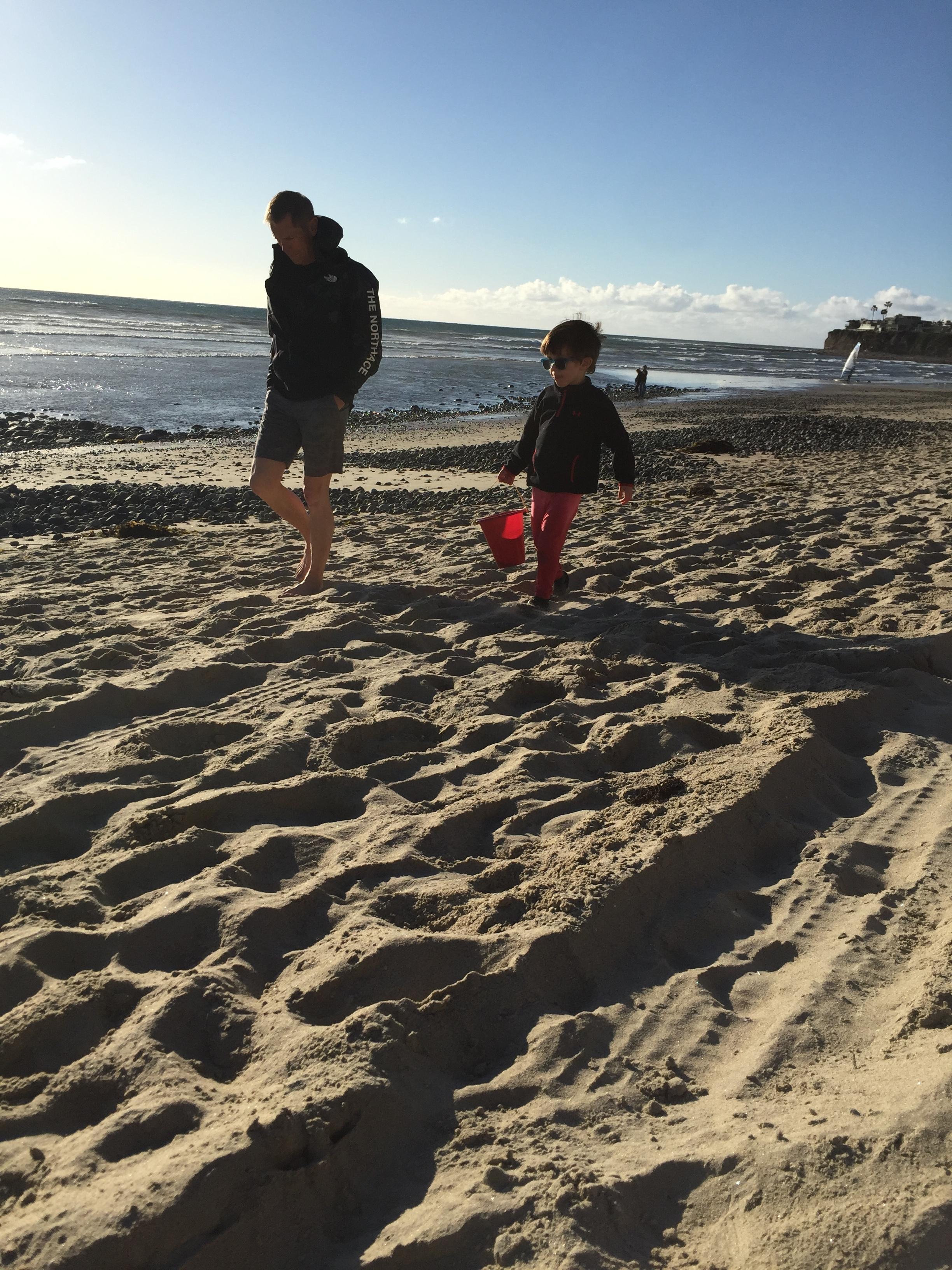 Grandpa Doug and Solomon filling holes with ocean water.
