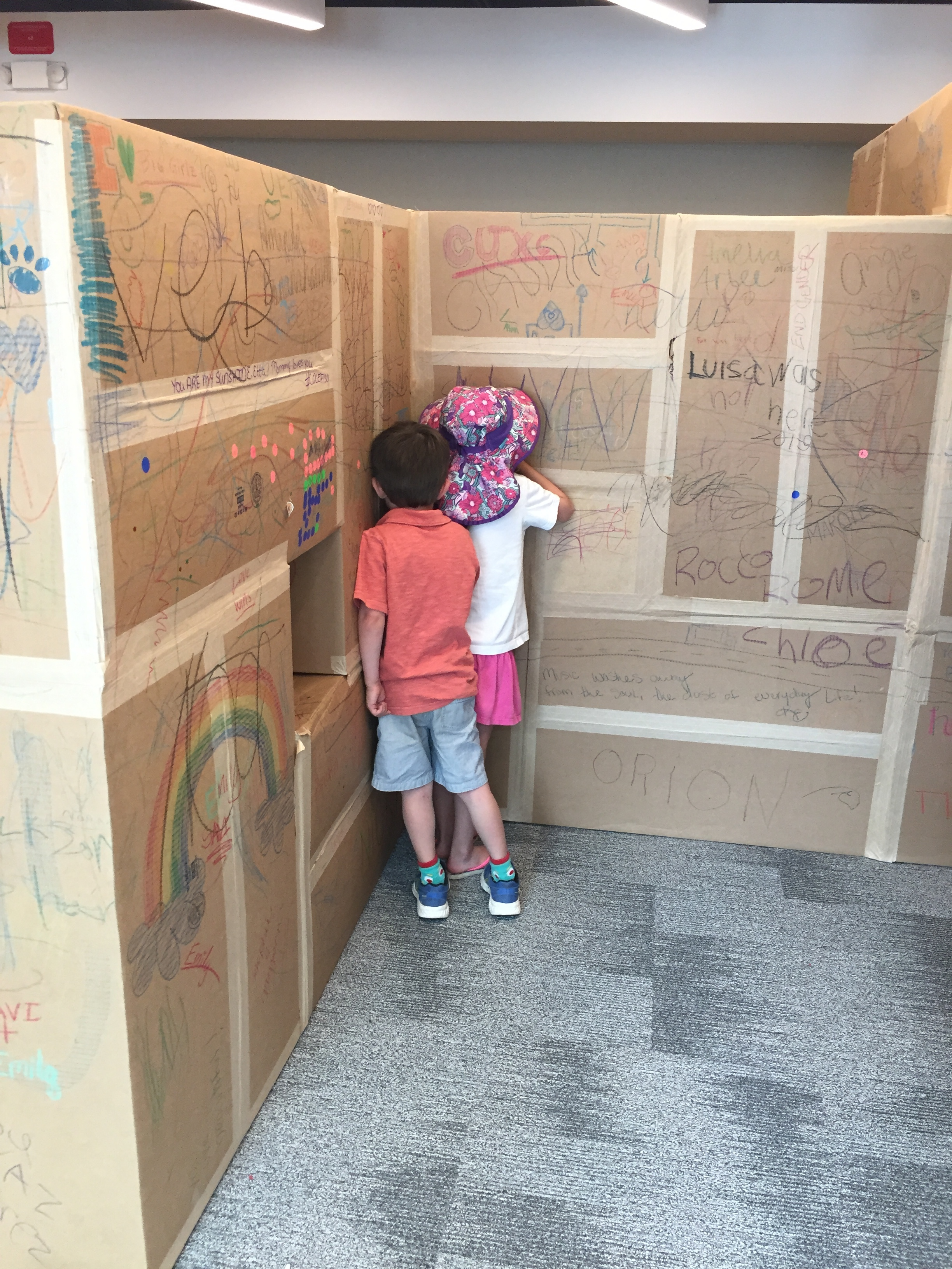 Playing hide and seek with new-found friend at Boulder History Museum cardboard maze.