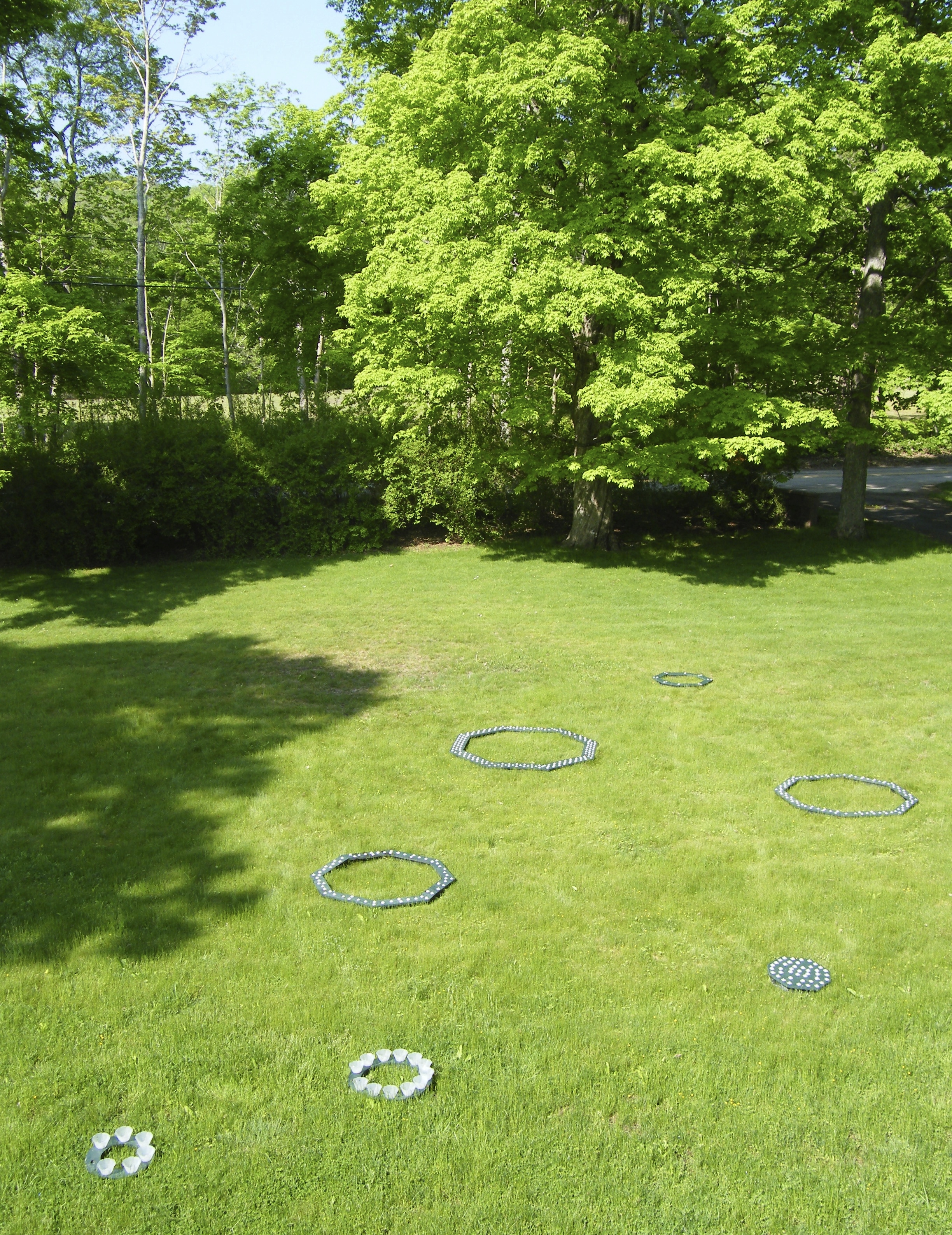 I constructed and installed these seven ephemeral  Floating Light Sculptures  during a May 2013 residency at I-Park Foundation in rural Connecticut. The residency allowed me to develop an idea dating to 1994, and to bring it to fruition.  The sculptures were octagons and circles, and they ranged in diameter from 9 inches to 5 ½ feet. They were best seen at night when their white glow was most intense. I was surprised that the forms maintained a quiet presence during the day. Equally unexpected was how the LED lights mimicked the moon's glow and color.  The floating sculptures appear in photographs as smaller, distant objects. Walking the trail around the pond led one quite close to where the light sculptures were installed, and the energy of the lights made size irrelevant.   Surrounded by forest, the sculptures floated in the pond's clear space, moving in concert with the wind. Nature subsumed these sculptures; once afloat, they belong more to the natural world than the man-made.   Materials: wood, screws and grommets, Styrofoam, paint, museum putty, and submersible LED lights lit by 48-hour batteries.    Many thanks to Lani Asuncion for the nighttime photos: #'s 6 – 10.