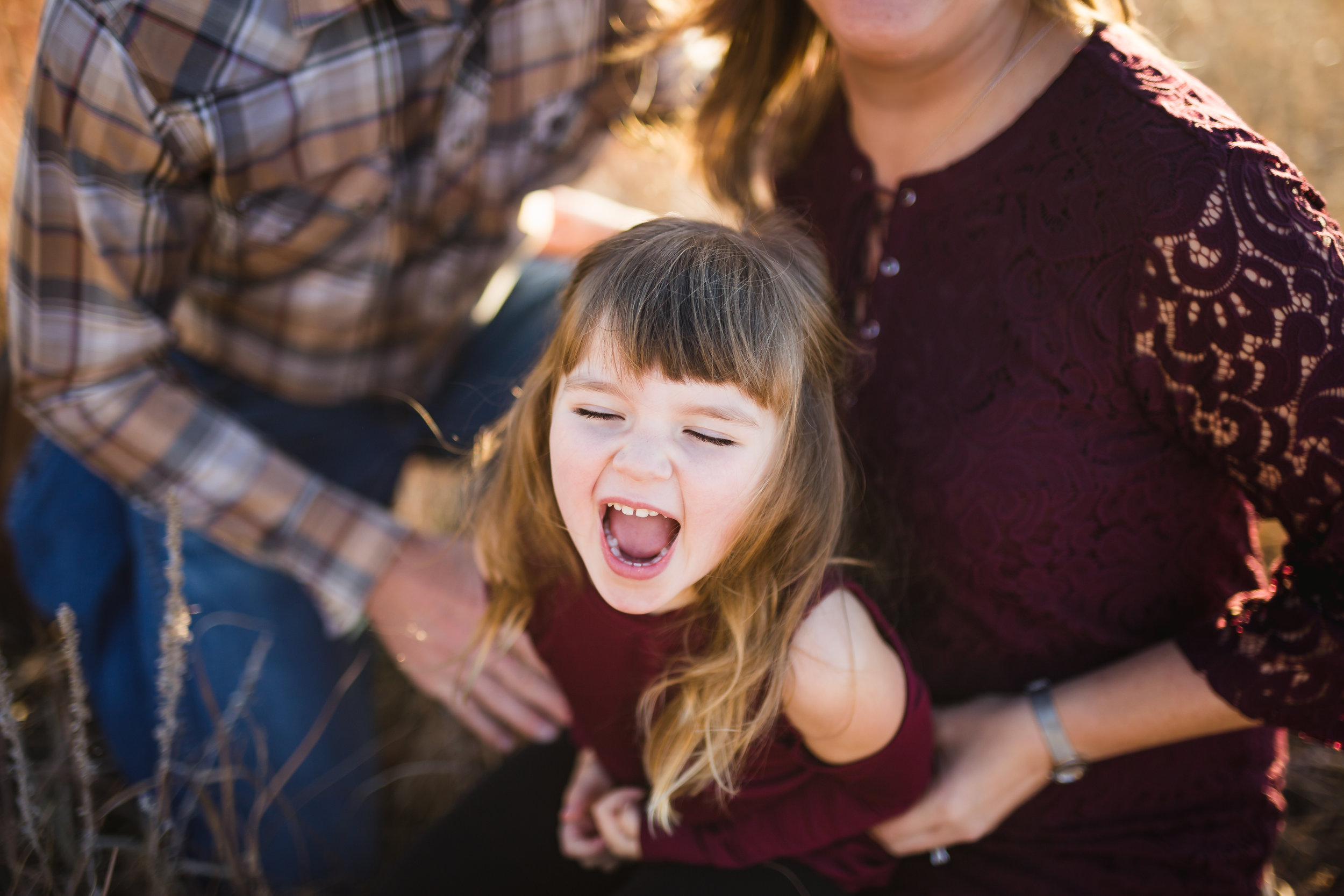 lifestyle family photo of child laughing in field by Lily Jean Photography