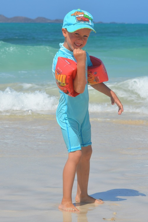 A young boy stands in the waves at the beach wearing water wings and sun protective clothing.