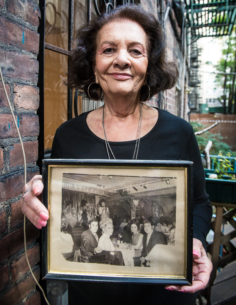 Arlene with a photo of her, her husband and friends