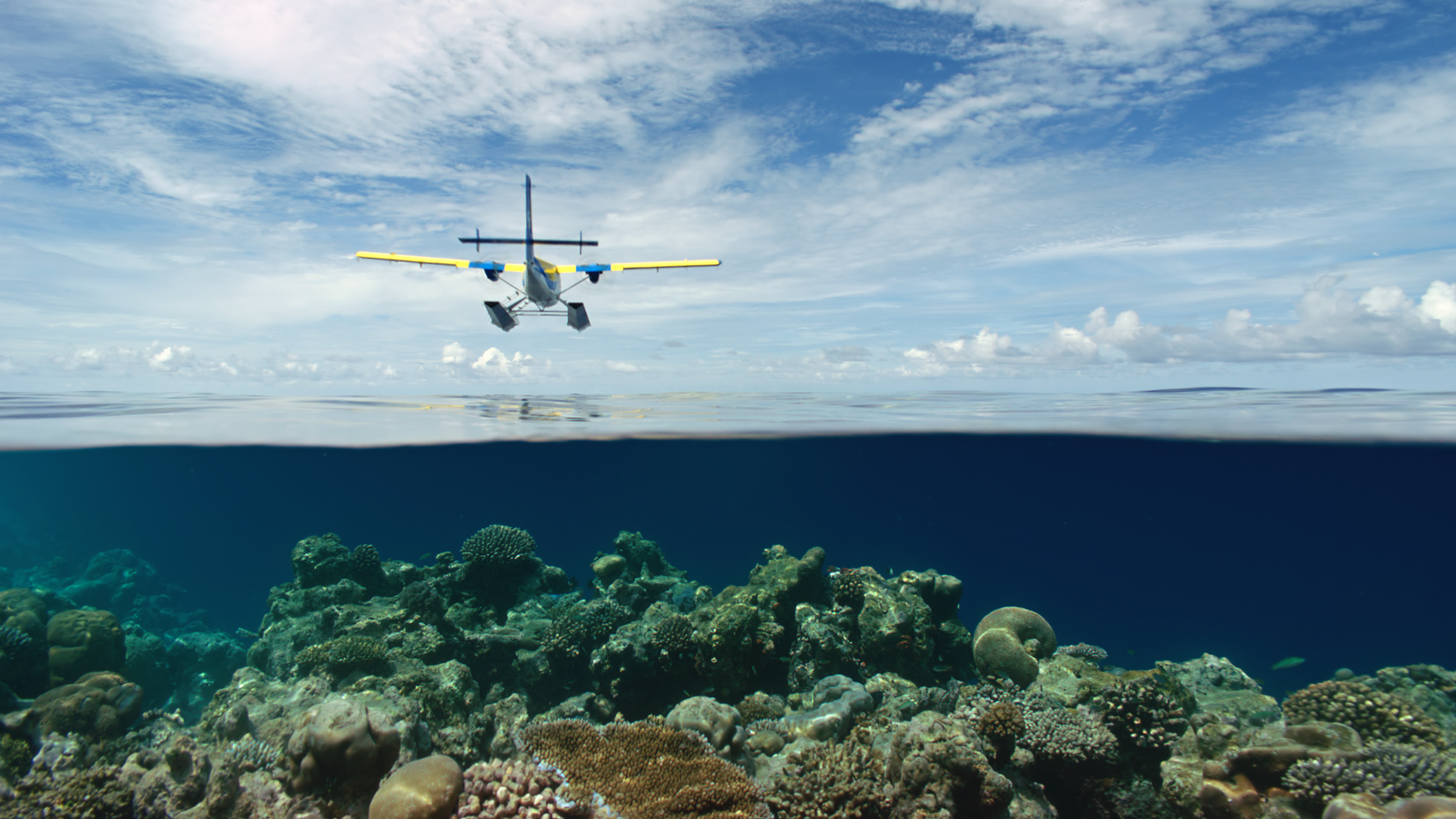 Twin Otter seaplane flying over the shallow waters of the Maldives.