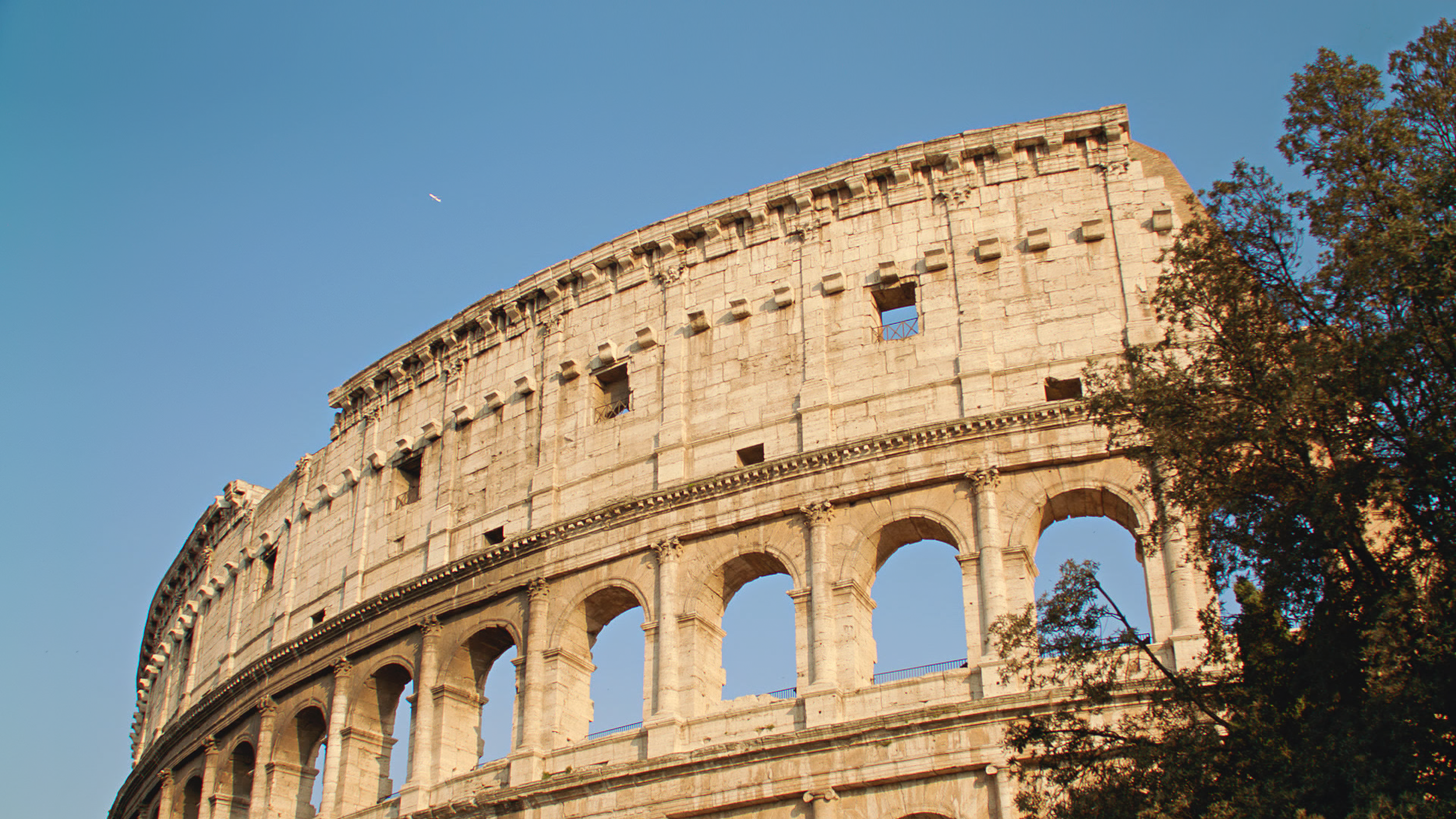 New and old: modern jet flying over the Colosseum in Rome, Italy.
