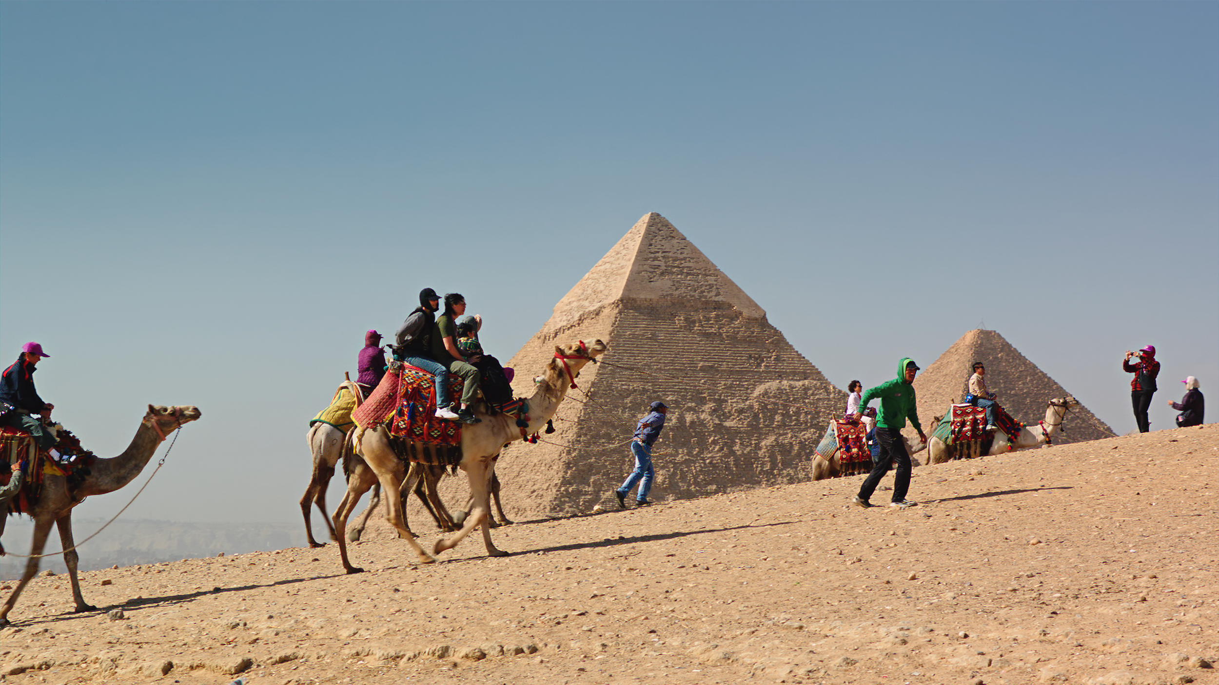 Tourists ride camels next to the Great Pyramid in Giza, Egypt.