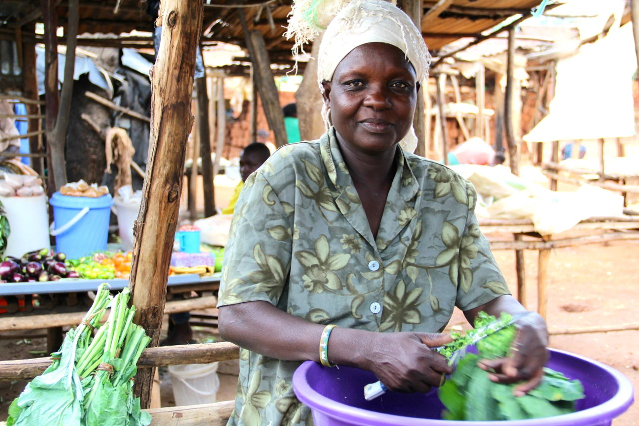 Magret cuts Skuma (leafy green that is similar to green) at her small stand in Namatala.