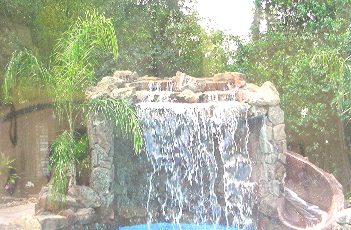 Grotto with incorporated slide  - Engineered steel reinforced gunite structure with approximately 20 tons of moss rock. slide coated with round penny tile.