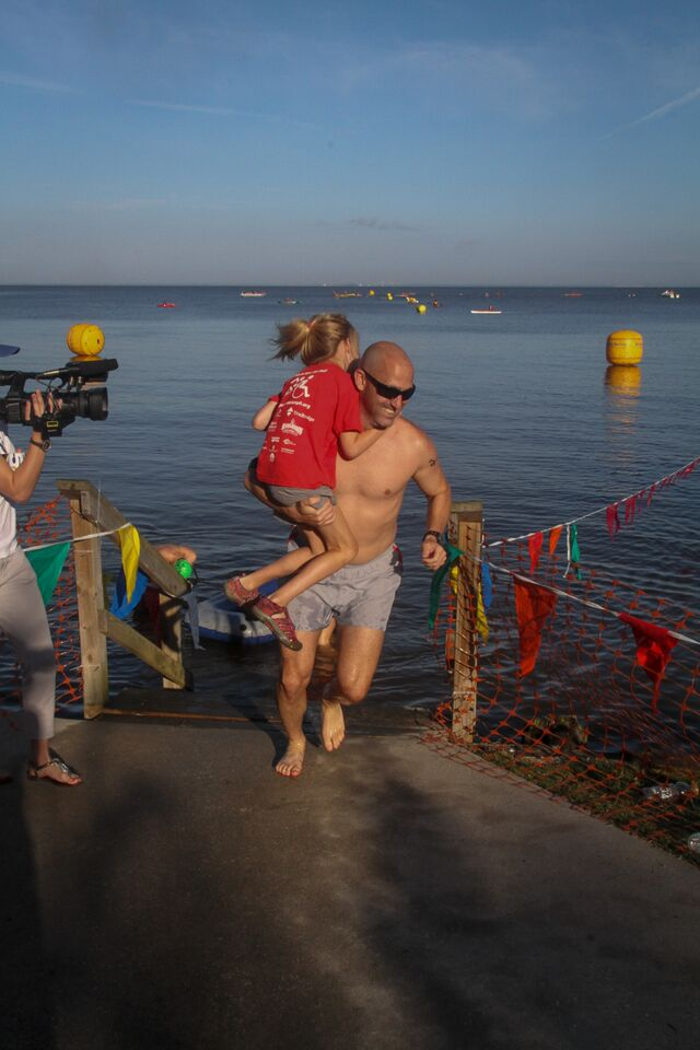 Jason Halbert with Captain Scarlett Ashurst exit the water in the 2015 Grandman Triathlon.