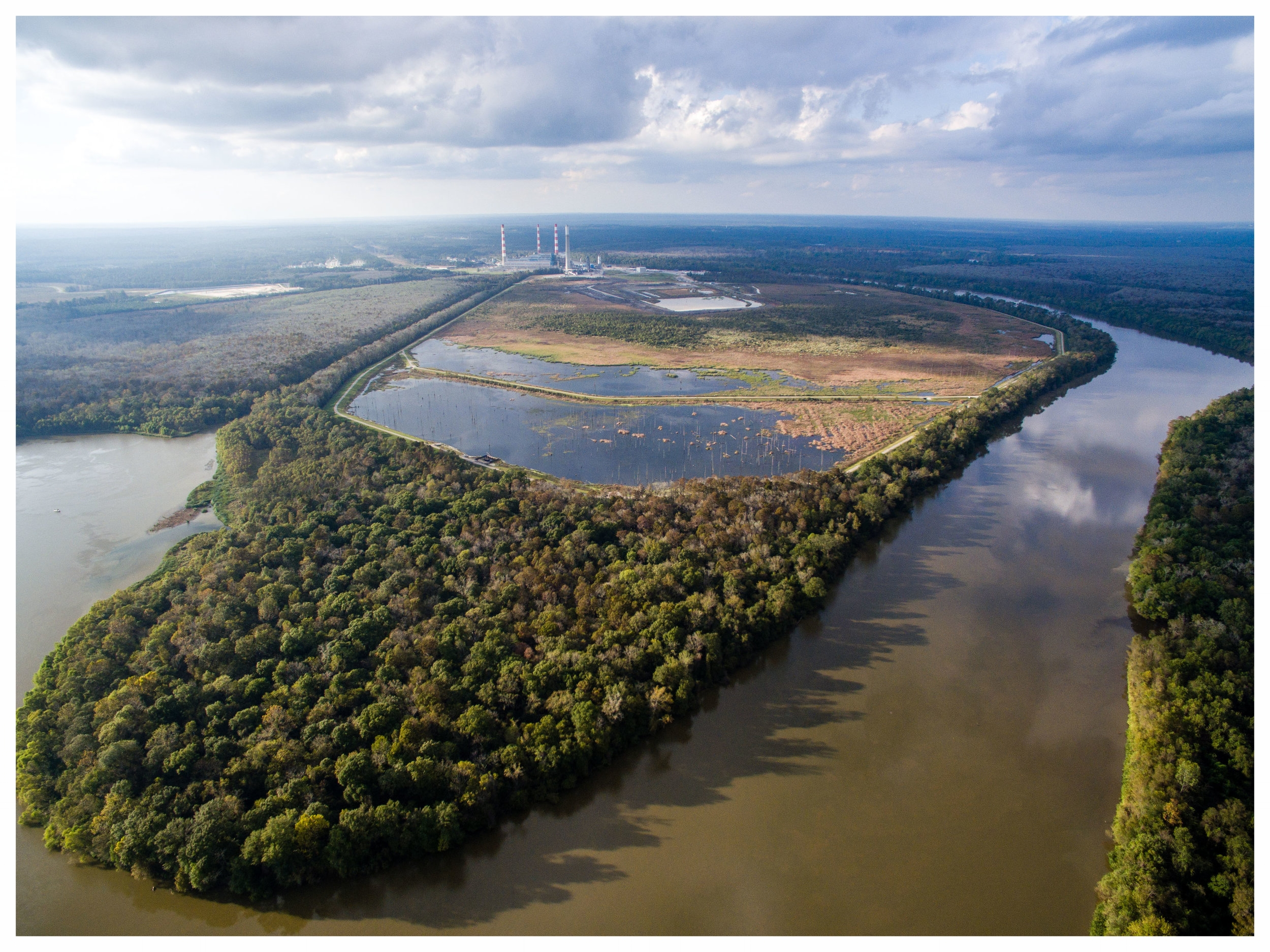 The  James M. Barry Electric Generating Plant , is located in Bucks, AL in North Mobile County. Coal ash from the facility is mixed with water and piped into a coal ash pond (pictured above). This pond is located immediately adjacent to the Mobile River and Mobile-Tensaw Delta and   contains more than 21 million tons of coal ash.