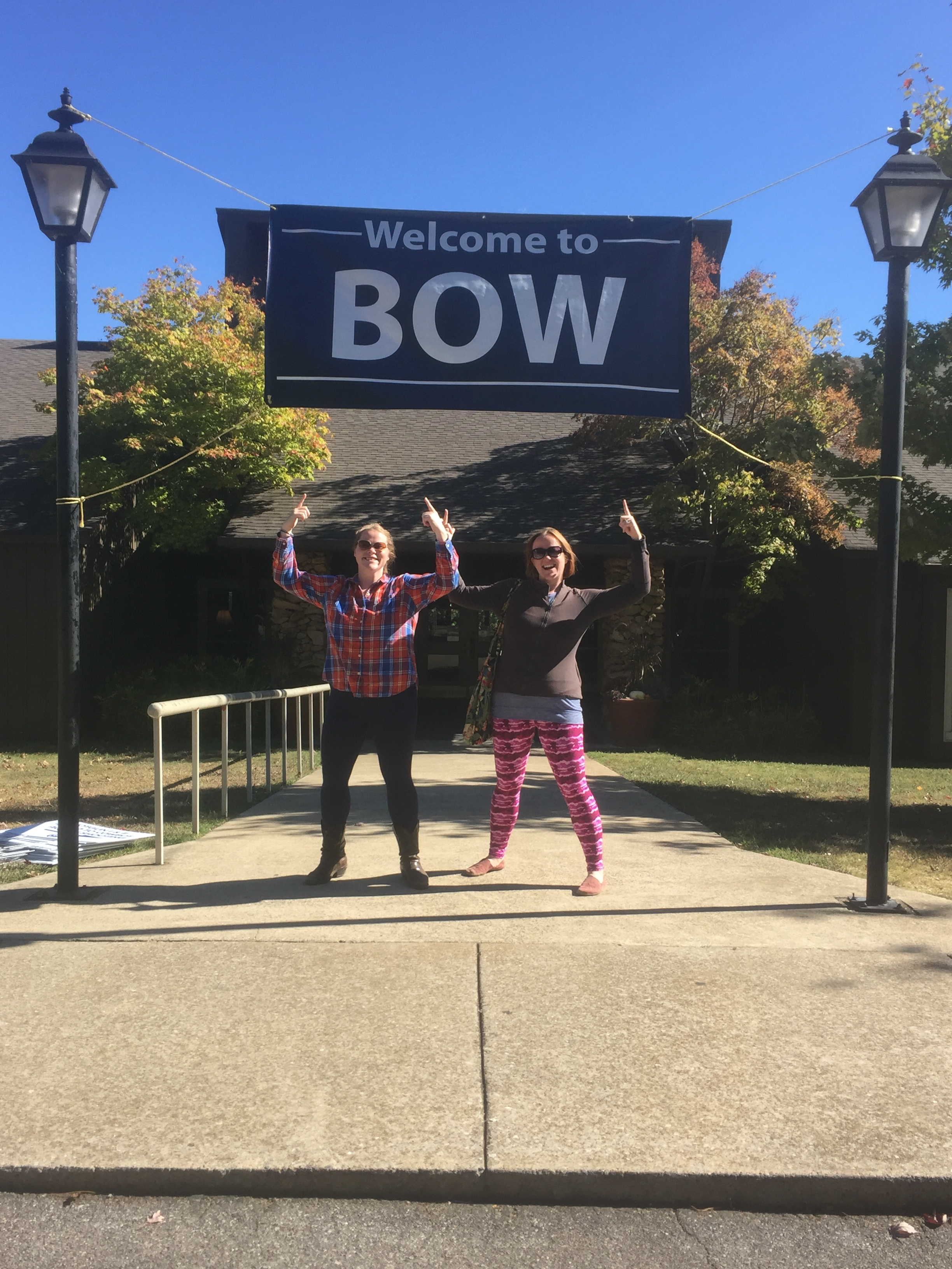"My sister Alison and I strike a pose under the ""Become an Outdoors-Woman"" welcome banner as we arrived to begin our journey for the weekend."