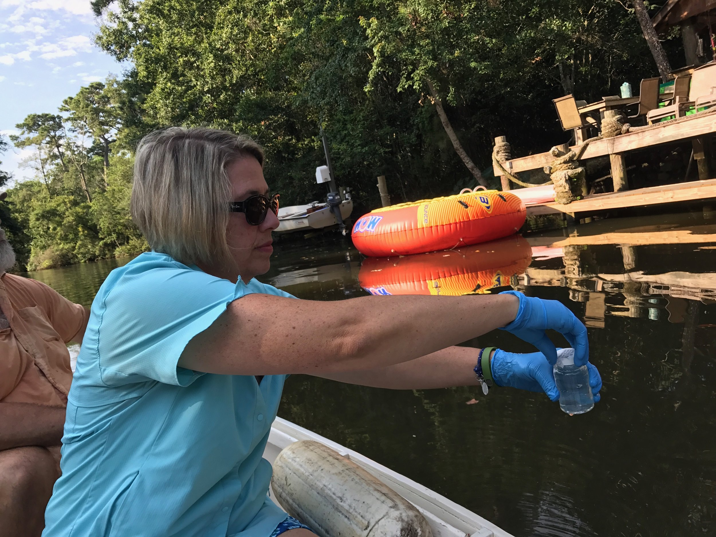 Executive Director Casi (kc) Callaway tests bacteria levels of Fly Creek following a sewage spill in August 2017.