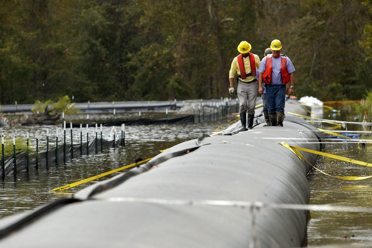 Crews on Monday monitor the temporary dam surrounding Santee Cooper's Grainger power station coal ash pond. They were sent out to squeeze air bubbles out of the dam in hopes of filling it with another inch or so of water. Paul Zoeller/Santee Cooper