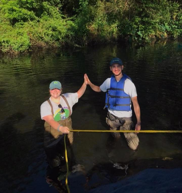 Justine Herlihy and Boris Kresevljak loading boats into One Mile Creek at Alabama Coastal Cleanup.